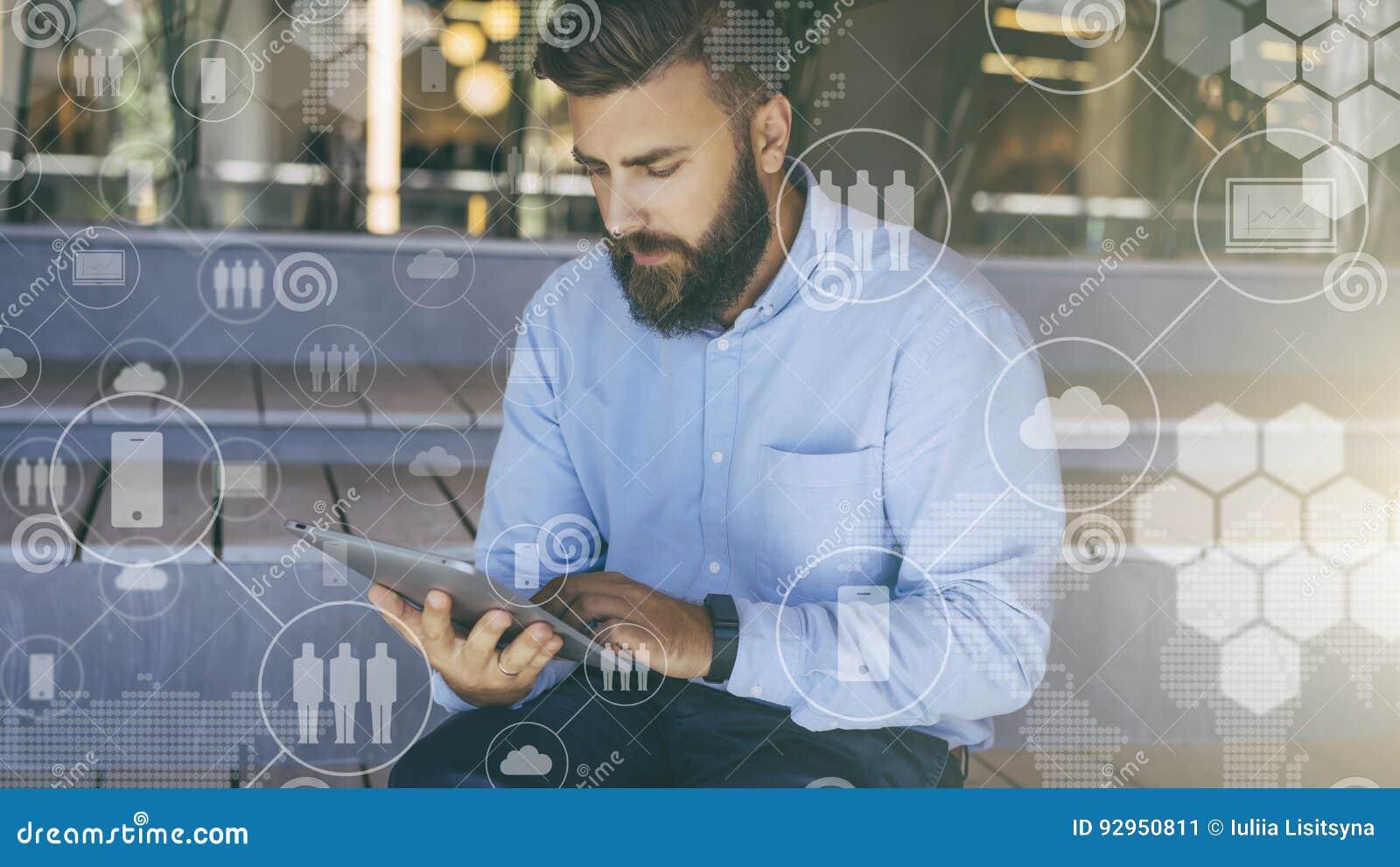 Le jeune homme barbu de hippie repose et utilise le comprimé numérique Dans le premier plan il y a les icônes virtuelles avec des