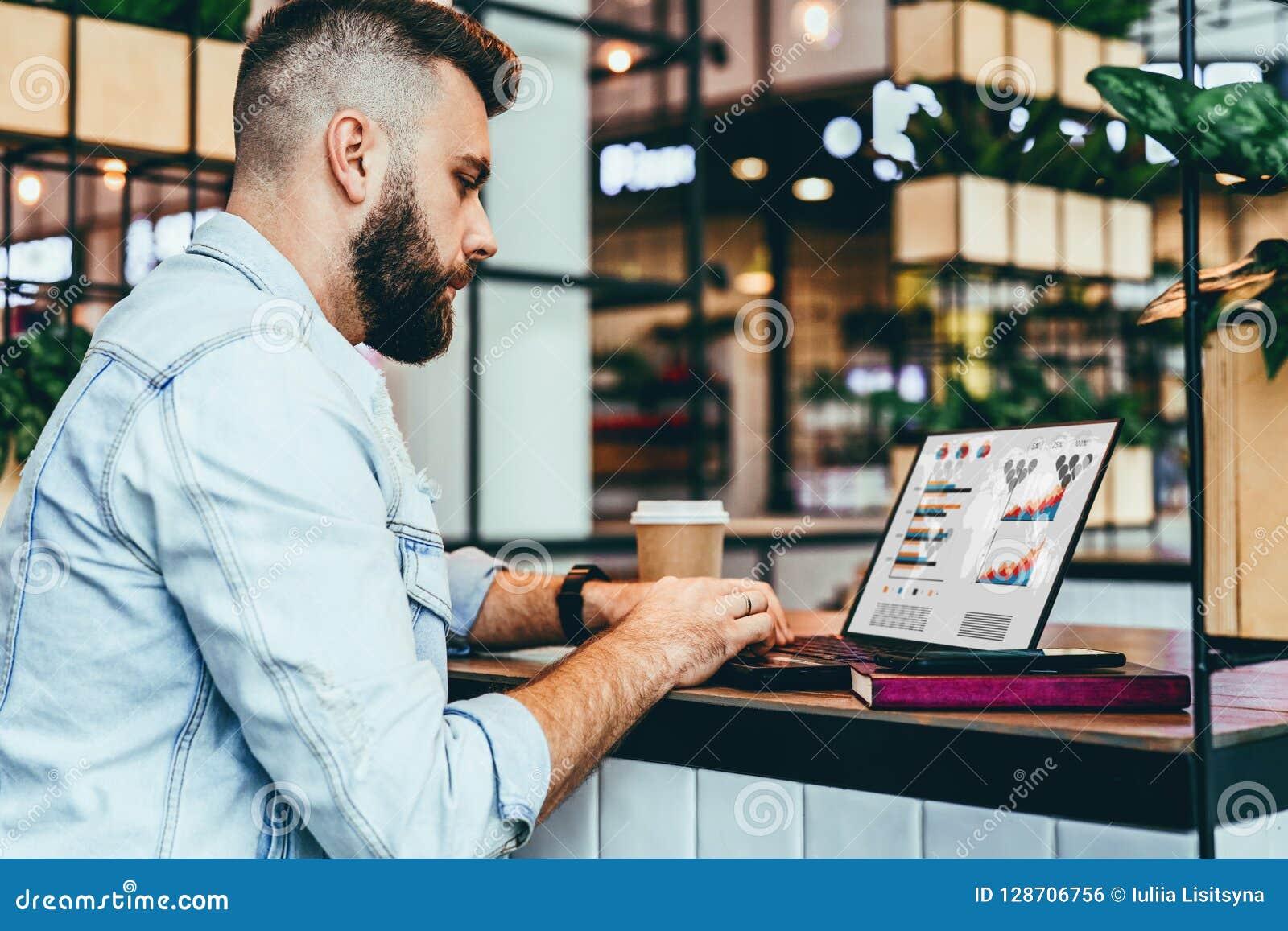 Le jeune homme barbu s assied en café, dactylographiant sur l ordinateur portable avec des diagrammes, les graphiques, diagrammes