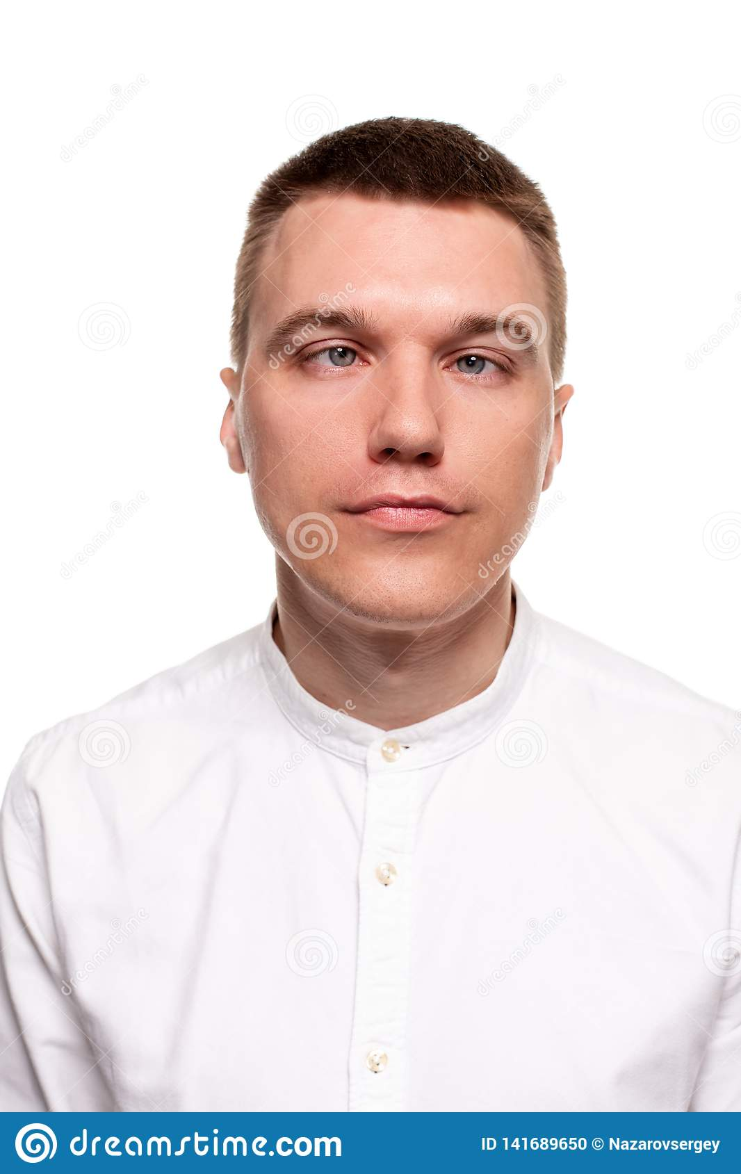 Le jeune homme beau de charme dans une chemise blanche fait des visages, tout en se tenant d isolement sur un fond blanc