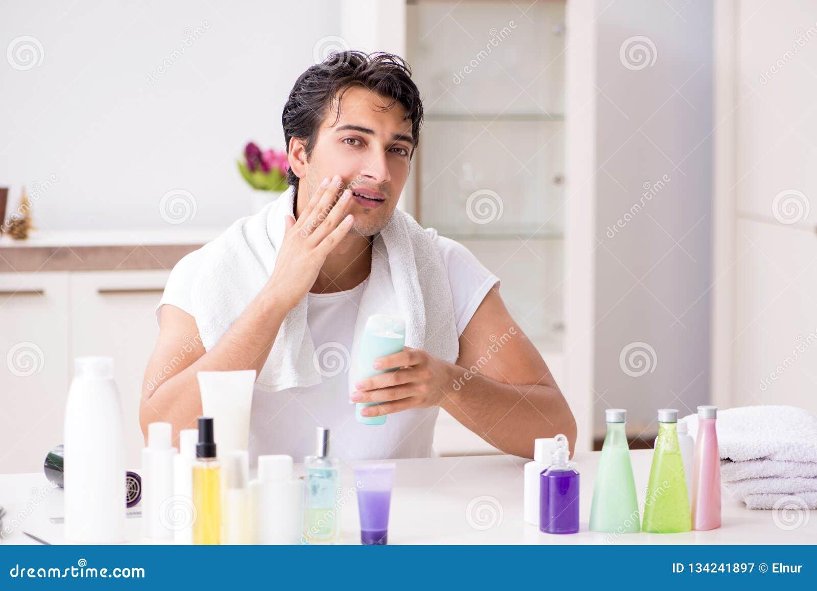 Le jeune homme bel dans la salle de bains dans le concept d hygiène