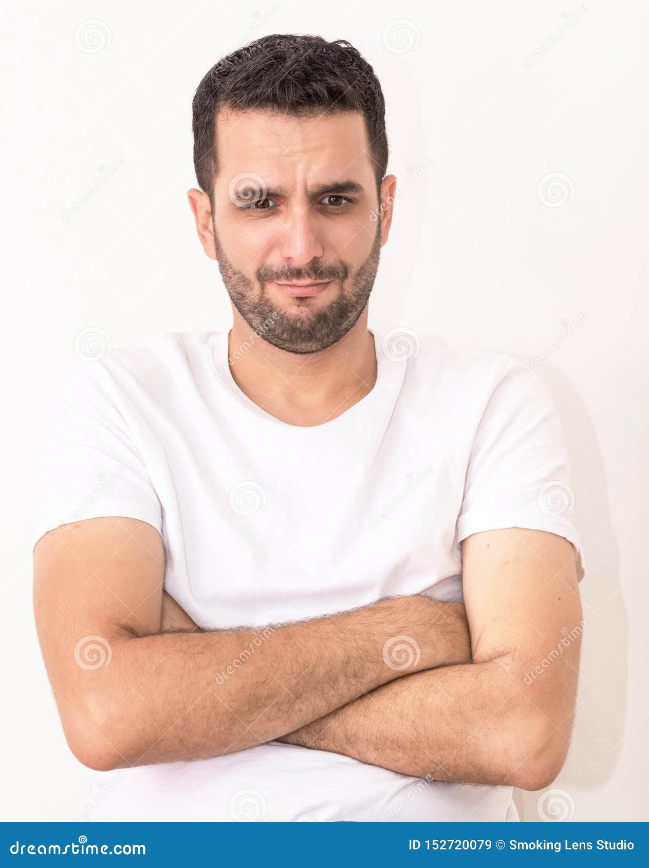 Le jeune homme caucasien avec ses mains a croisé, il semble blessé et triste