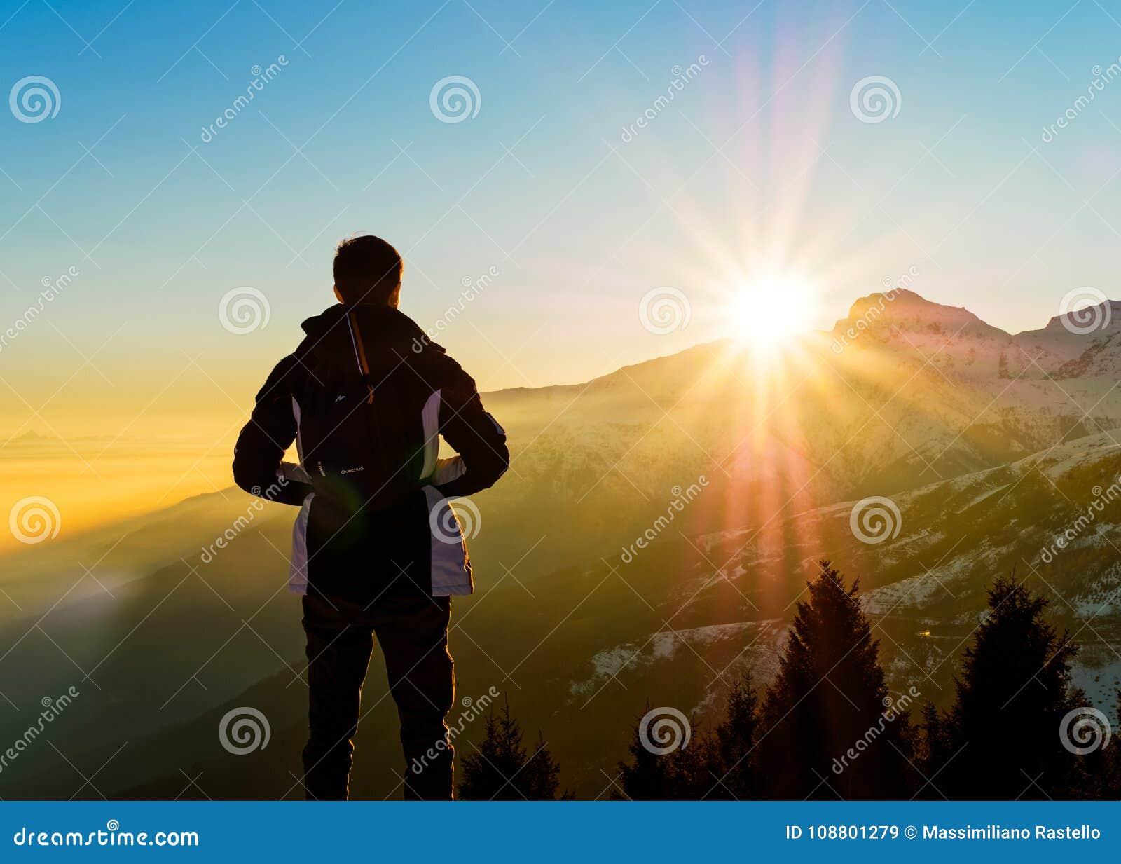 Le jeune homme contemplent le coucher du soleil sur les Alpes