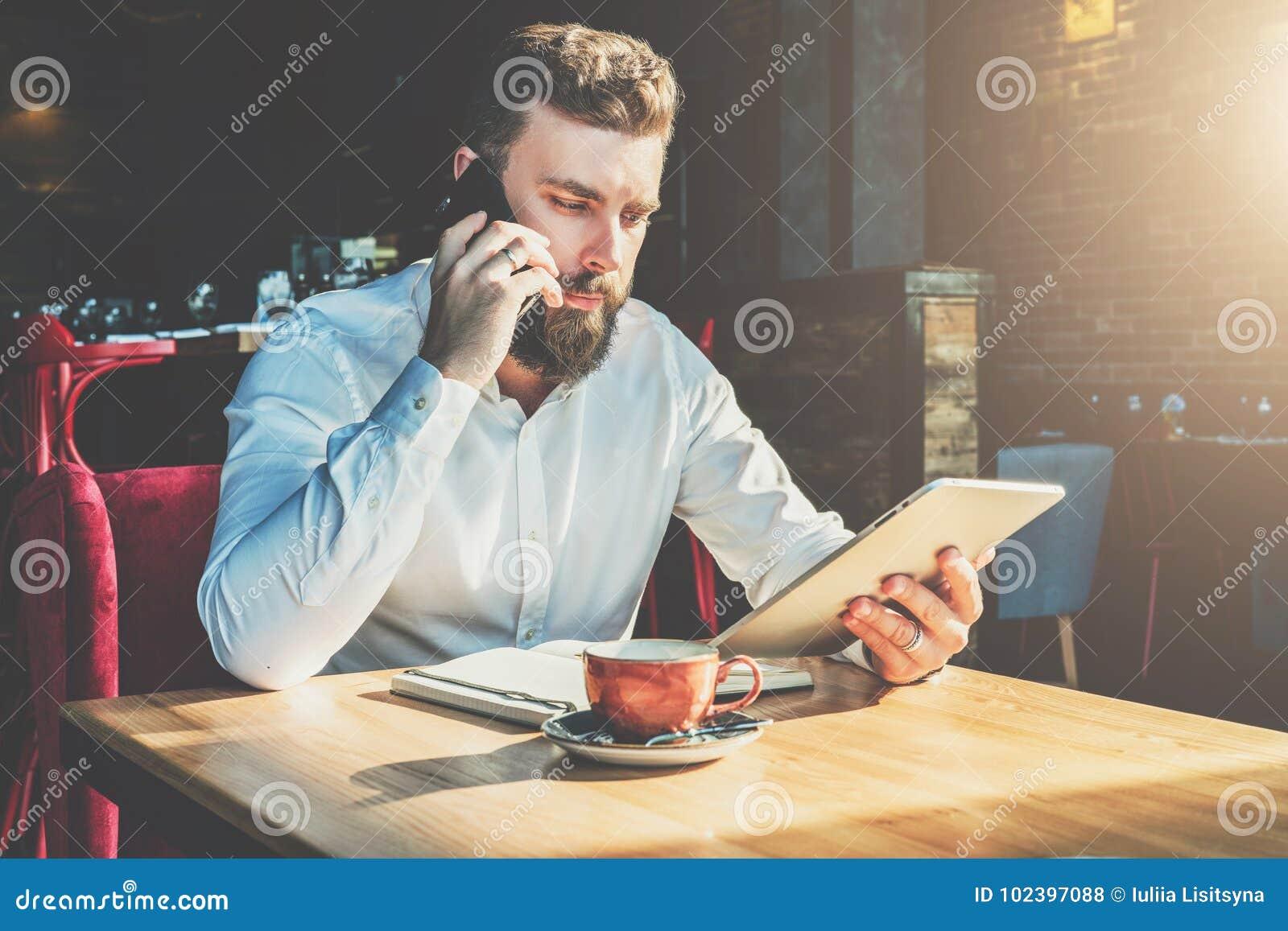 Le jeune homme d affaires barbu s assied en café à la table, parlant au téléphone portable, tenant la tablette L homme travaille