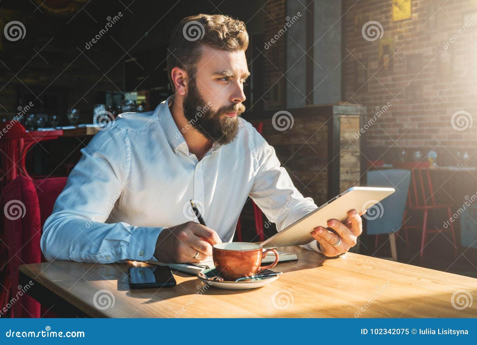 Le jeune homme d affaires barbu s assied en café à la table, tient la tablette et écrit dans le carnet