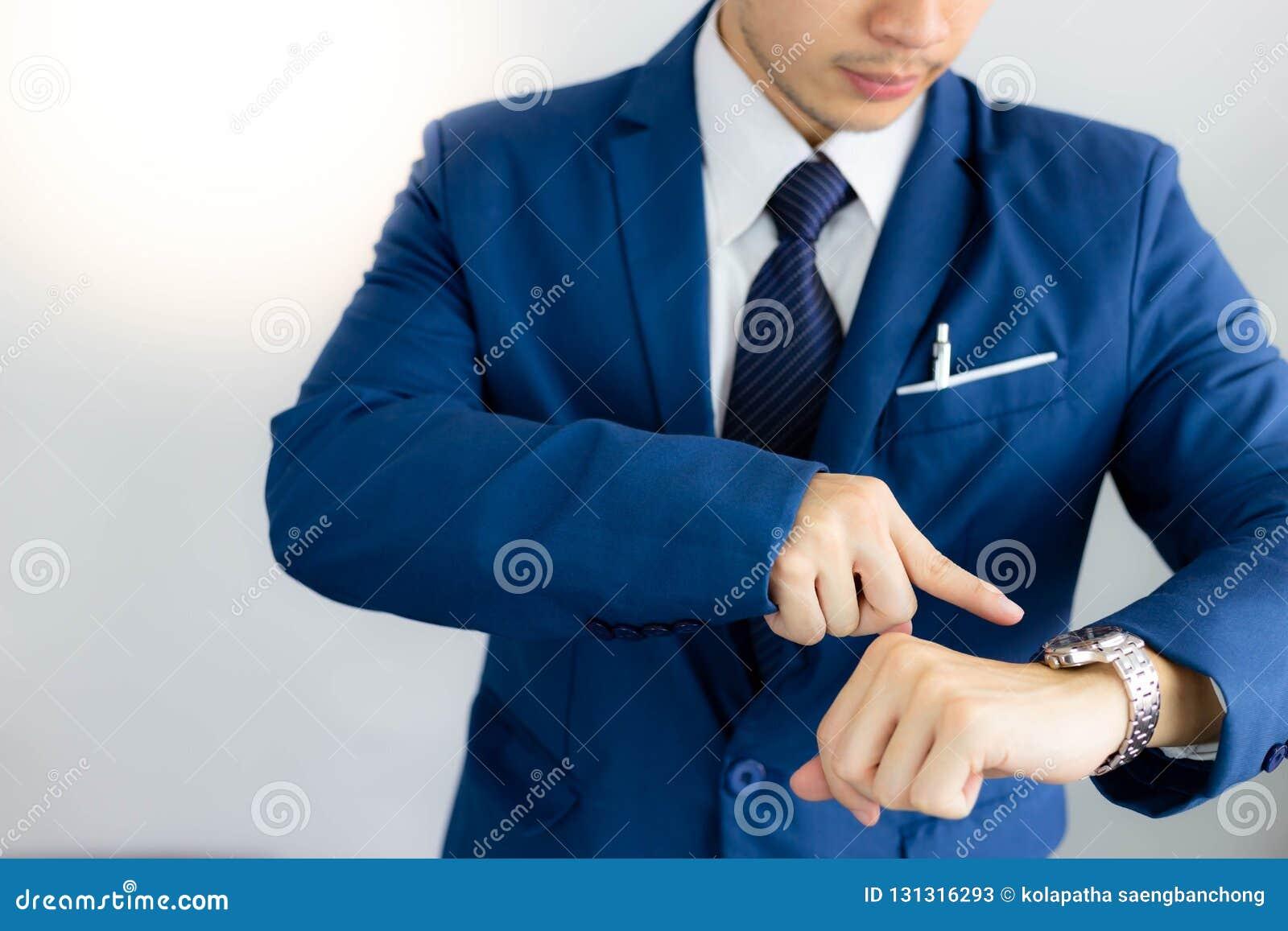 Le jeune homme d affaires beau attirant regarde le temps sur le wri