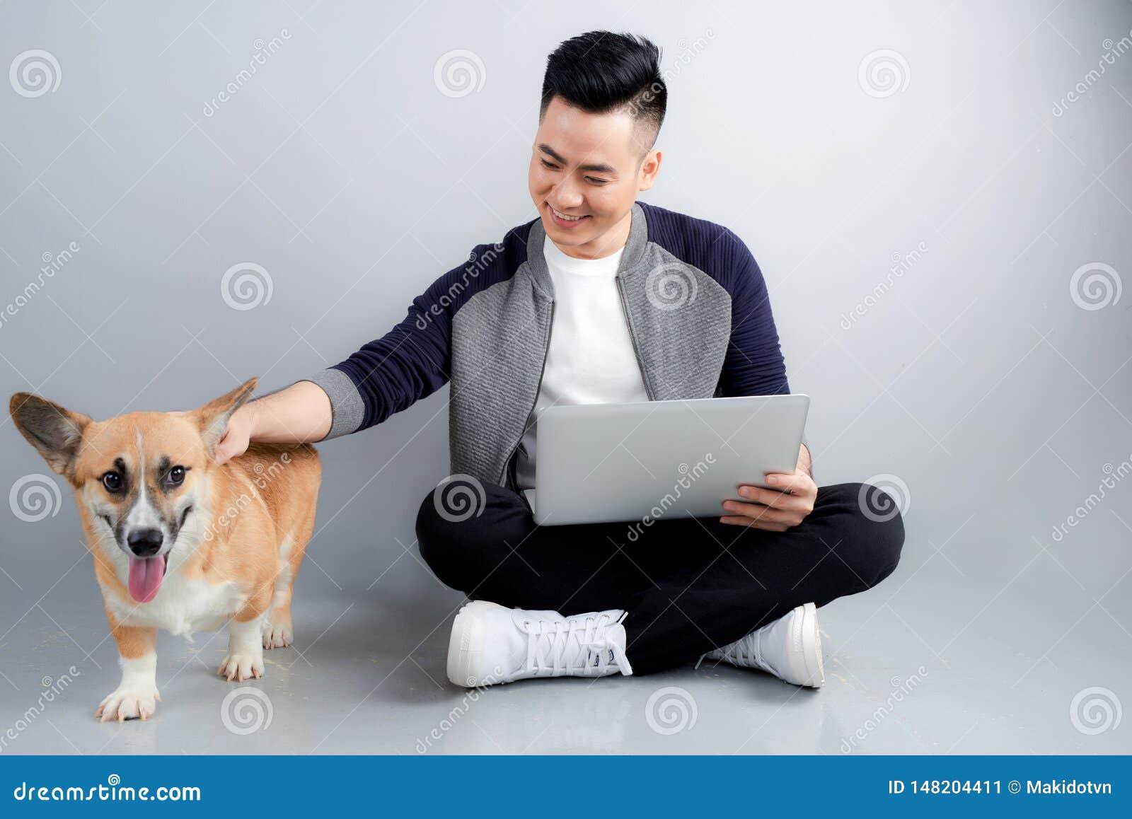 Le jeune homme d affaires beau utilise l ordinateur portable tout en se reposant avec son chien sur le plancher
