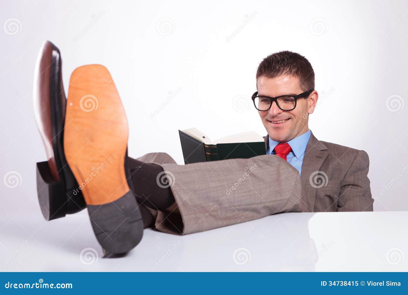 Le jeune homme d affaires lit un livre avec des pieds sur le