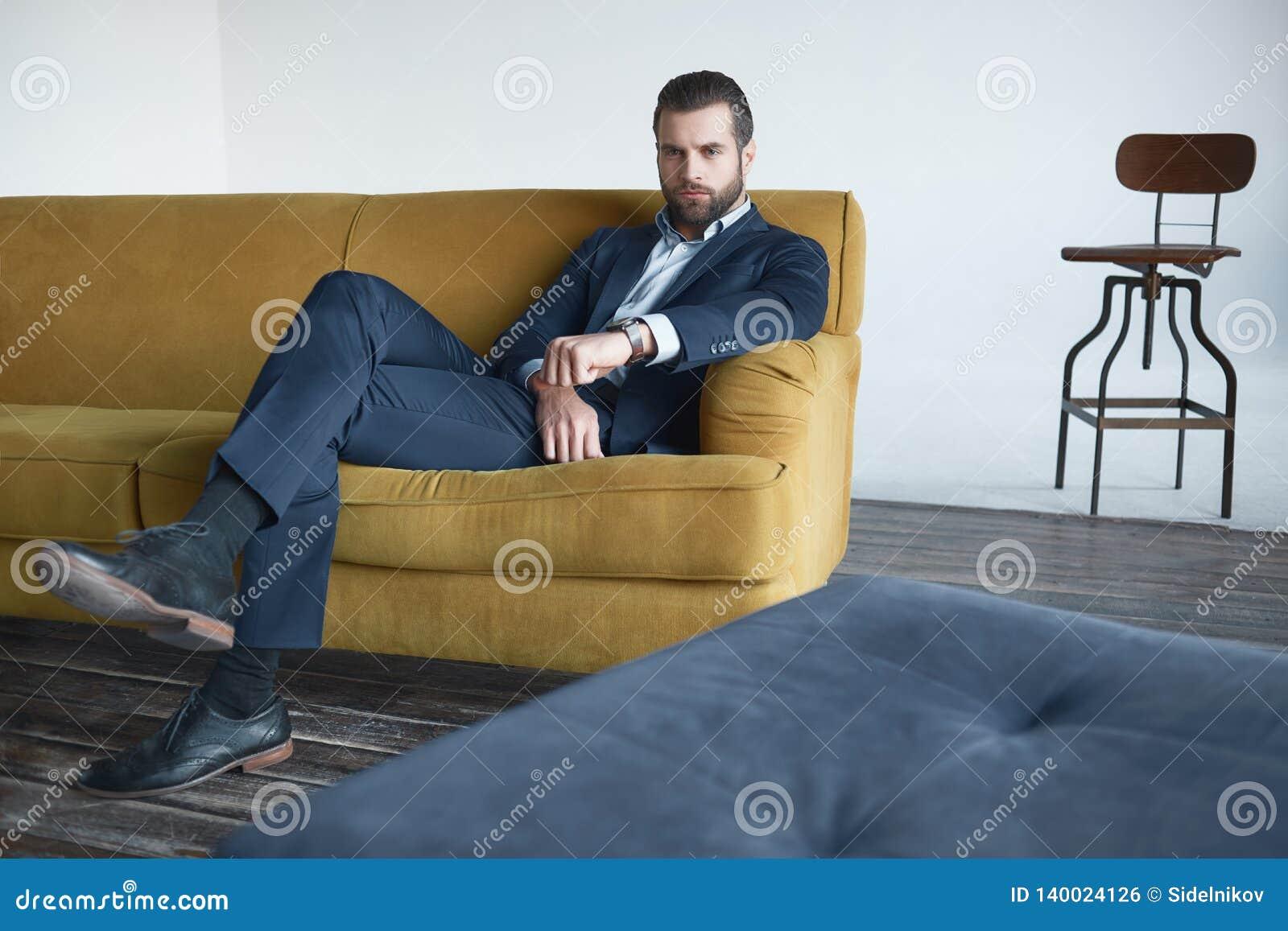 Le jeune homme d affaires réussi s assied sur le sofa de bureau et regarde la caméra