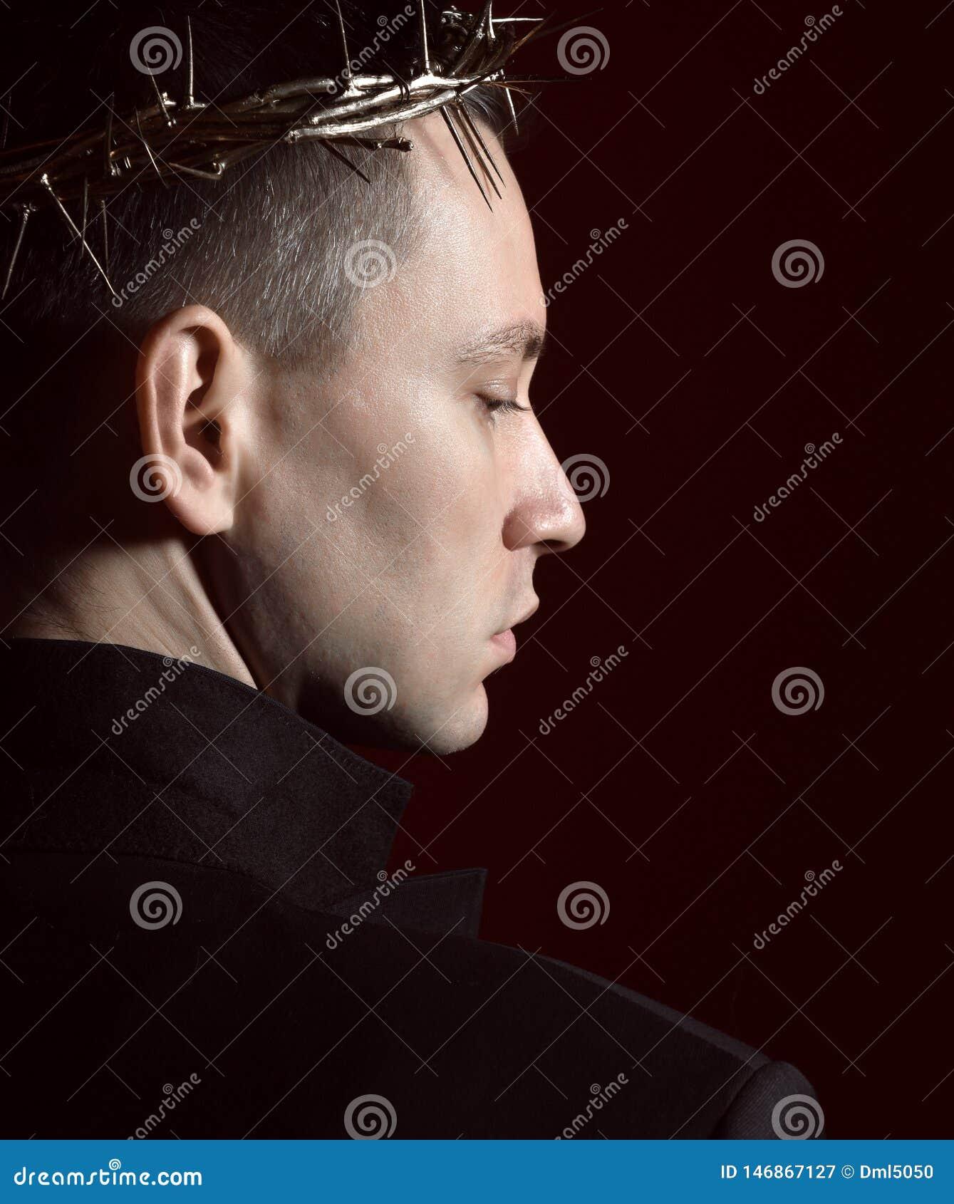 Le jeune homme dans la couronne des épines, du martyre et du jacke noir de costume se tient de nouveau à nous avec la tête tourné