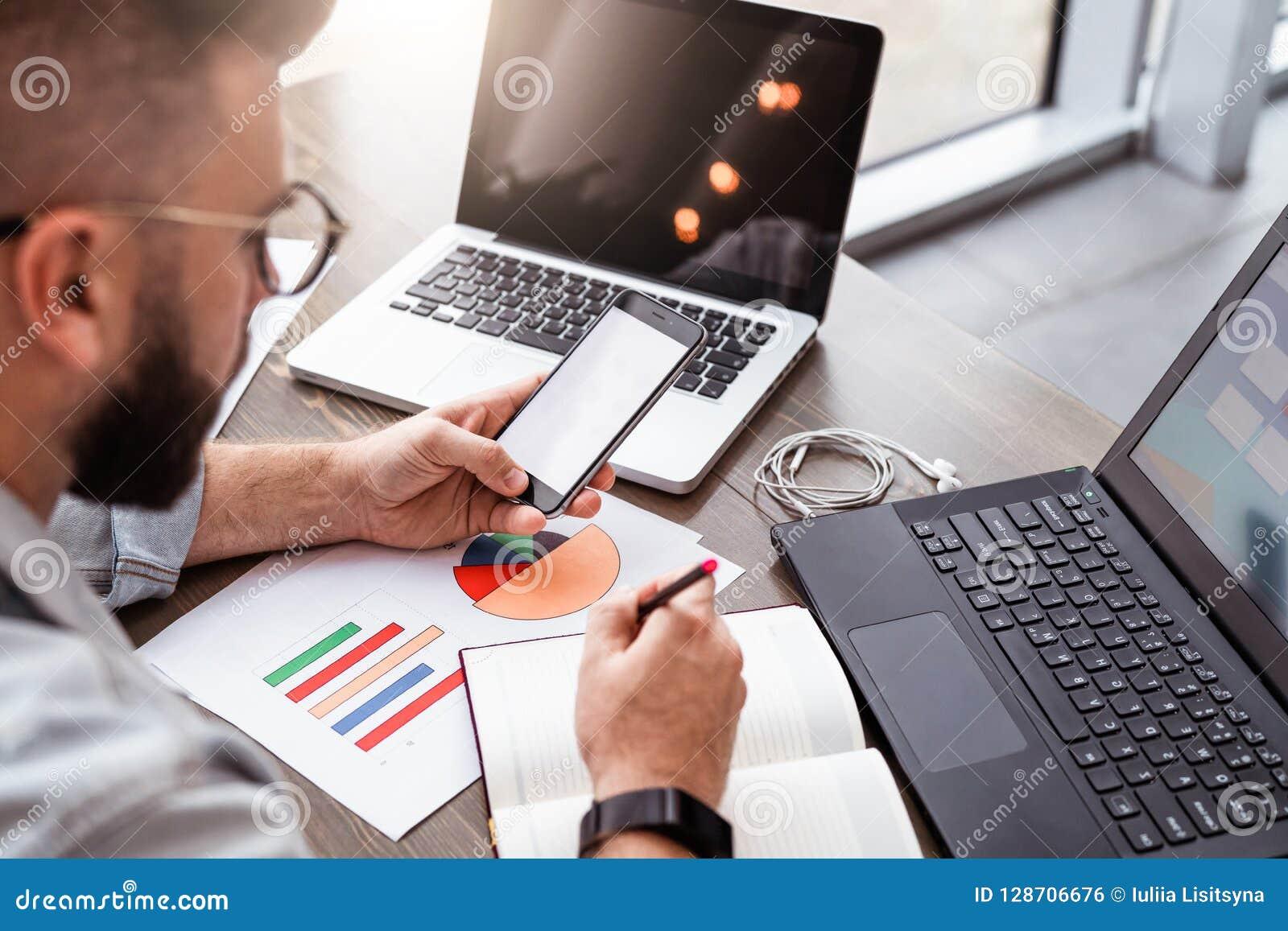 Le jeune homme, entrepreneur, indépendant s assied dans le bureau à la table, utilise le smartphone, travaillant sur l ordinateur