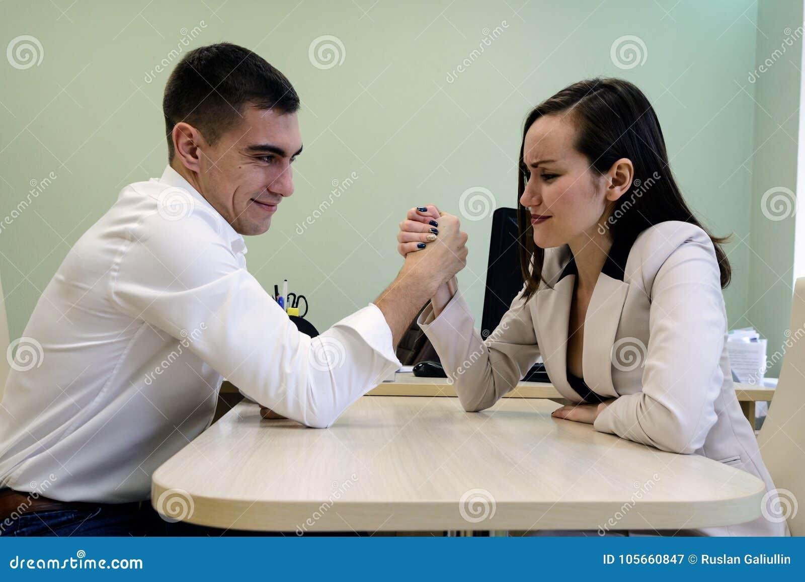 Le jeune homme et la femme luttent sur ses mains au bureau dans le
