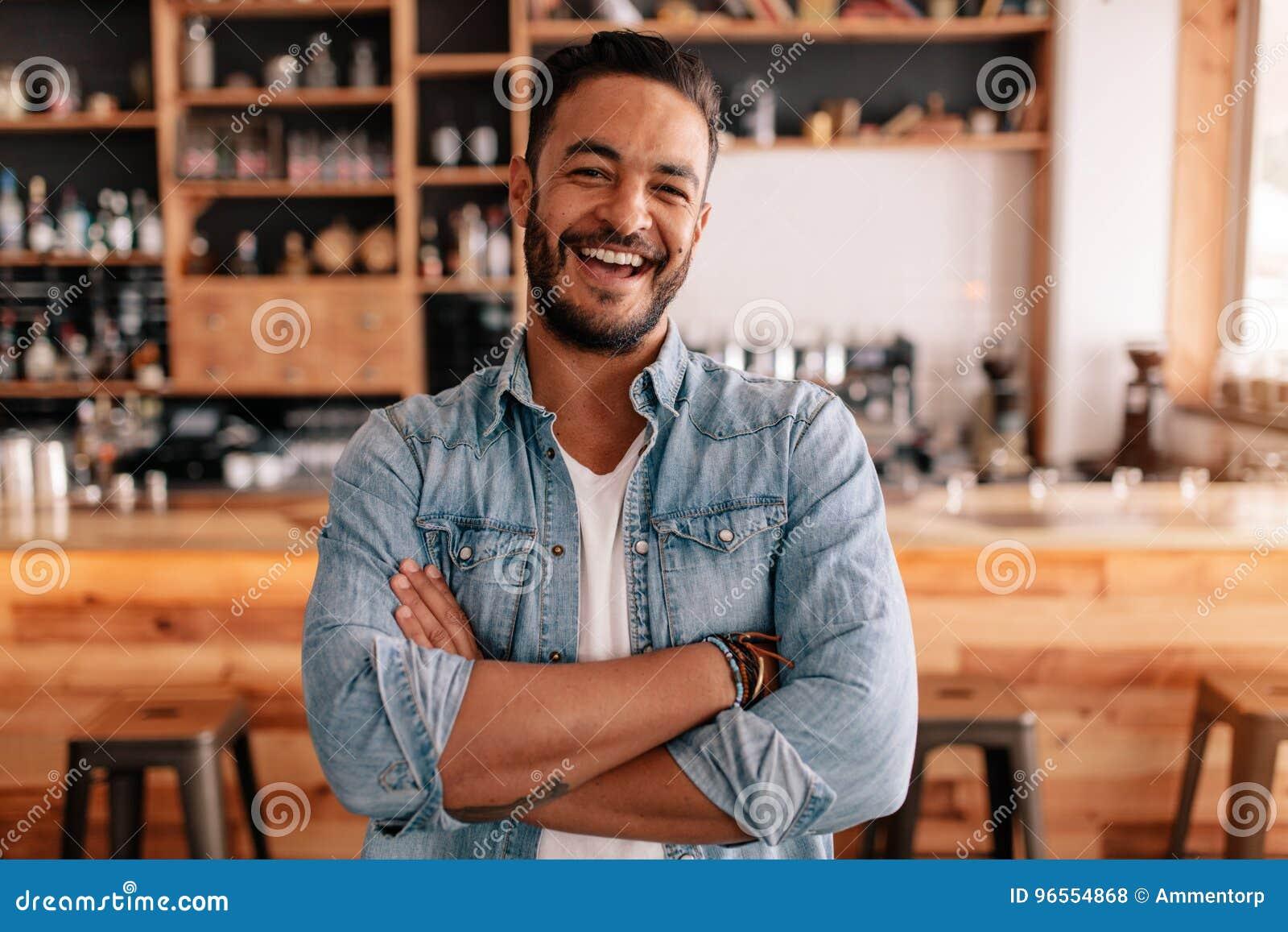 Le jeune homme heureux se tenant avec ses bras a croisé dans un café