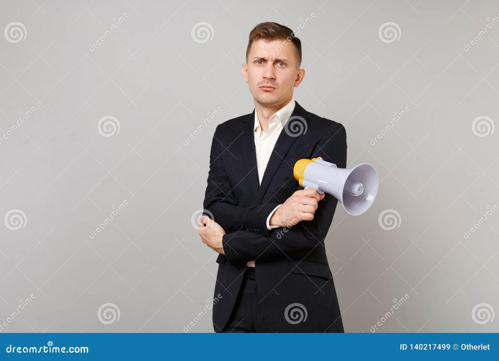 Le jeune homme indifférent d affaires dans le costume noir classique, chemise tenant des mains avec le mégaphone s est plié d iso