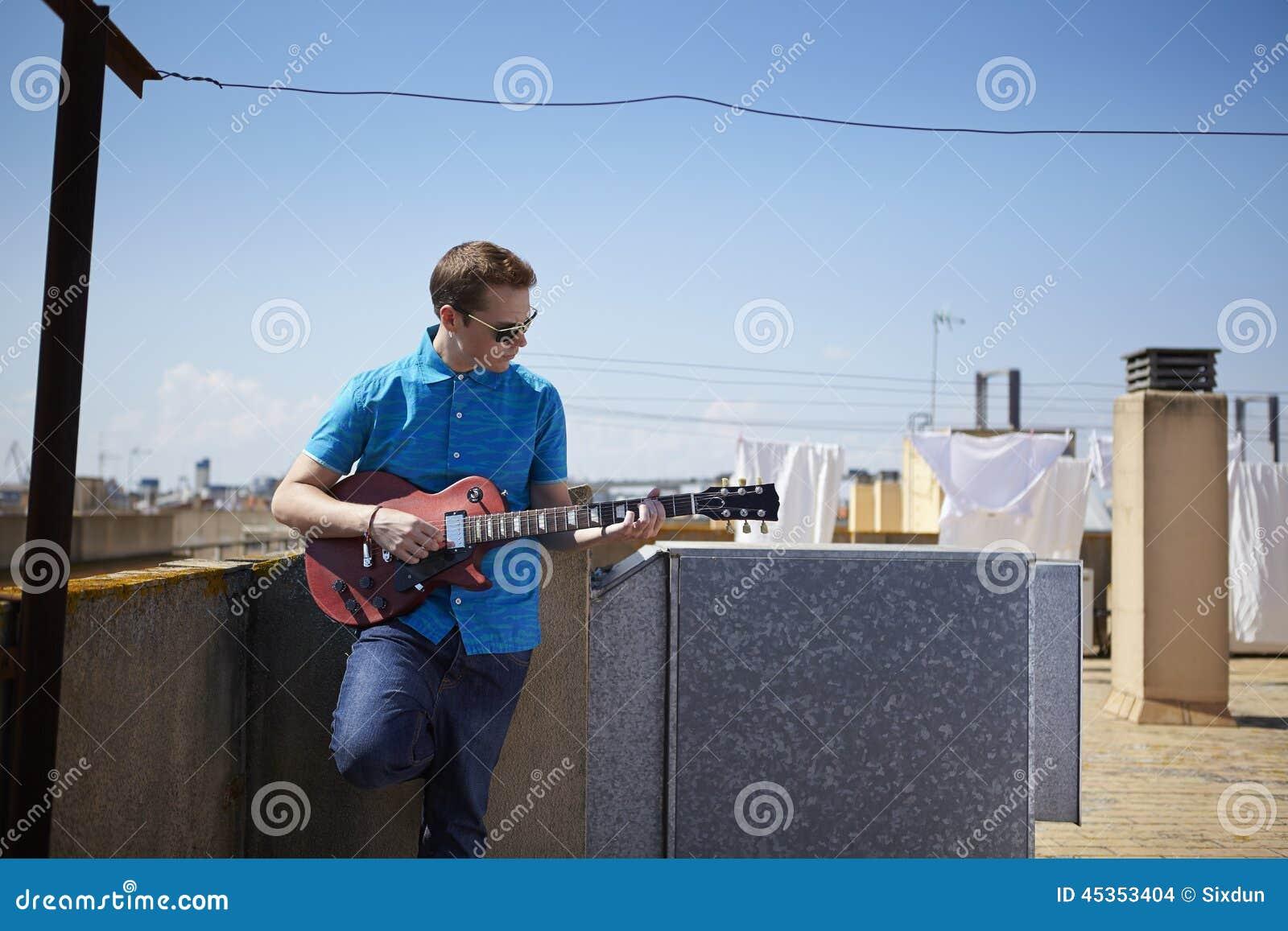 Le jeune homme joue la guitare sur la terrasse de toit