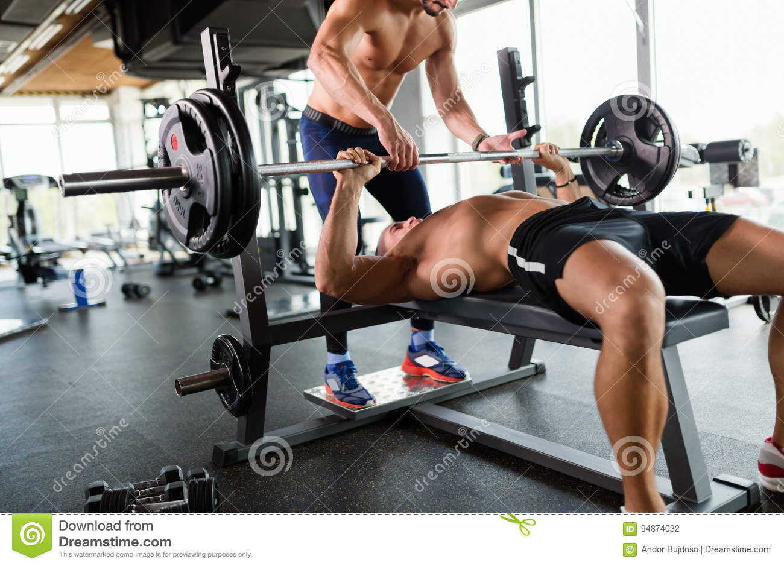 Le jeune homme musculaire beau faisant le banc à presse et obtient l aide