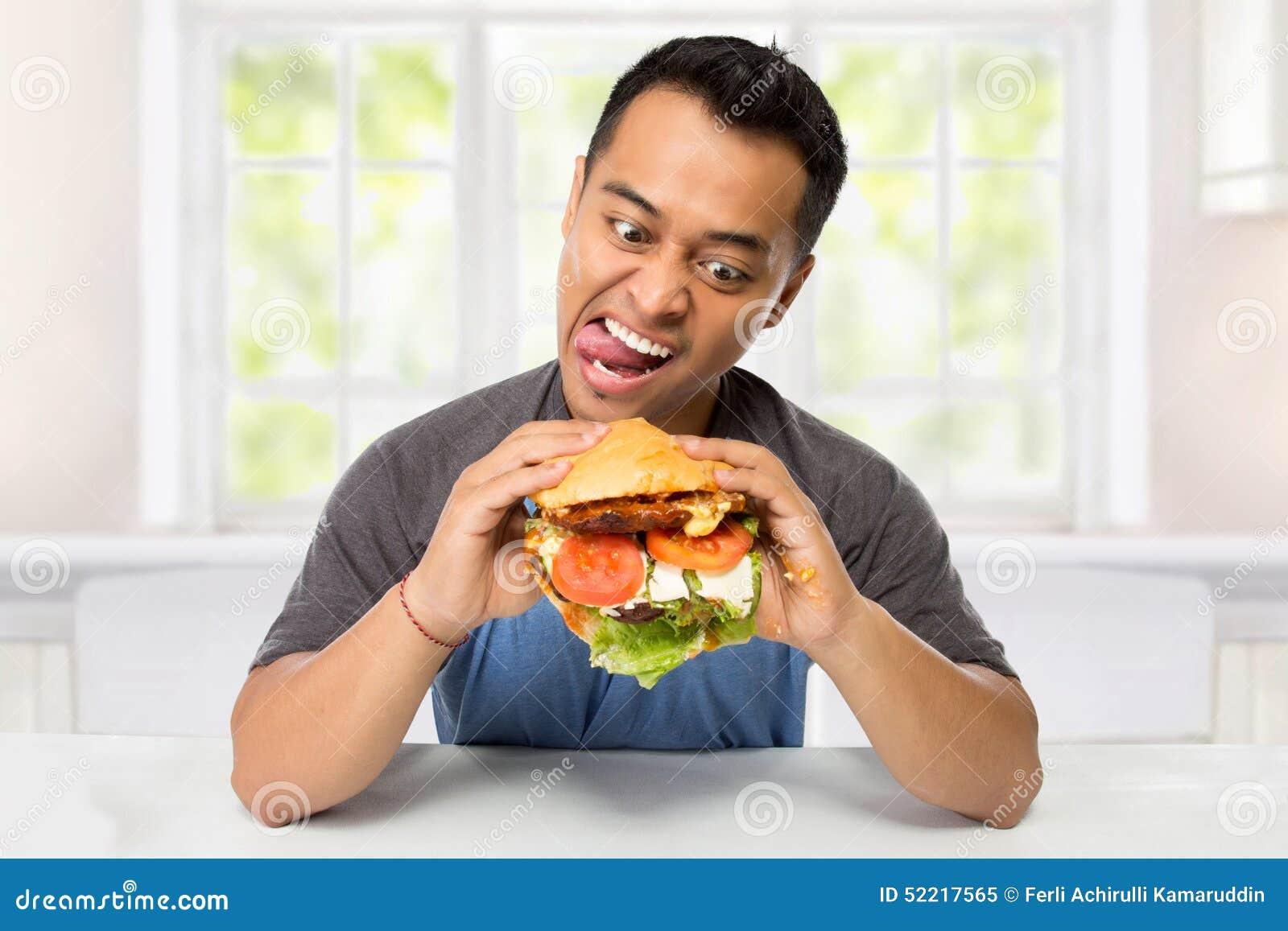 Le jeune homme ont un grand désir de manger un hamburger