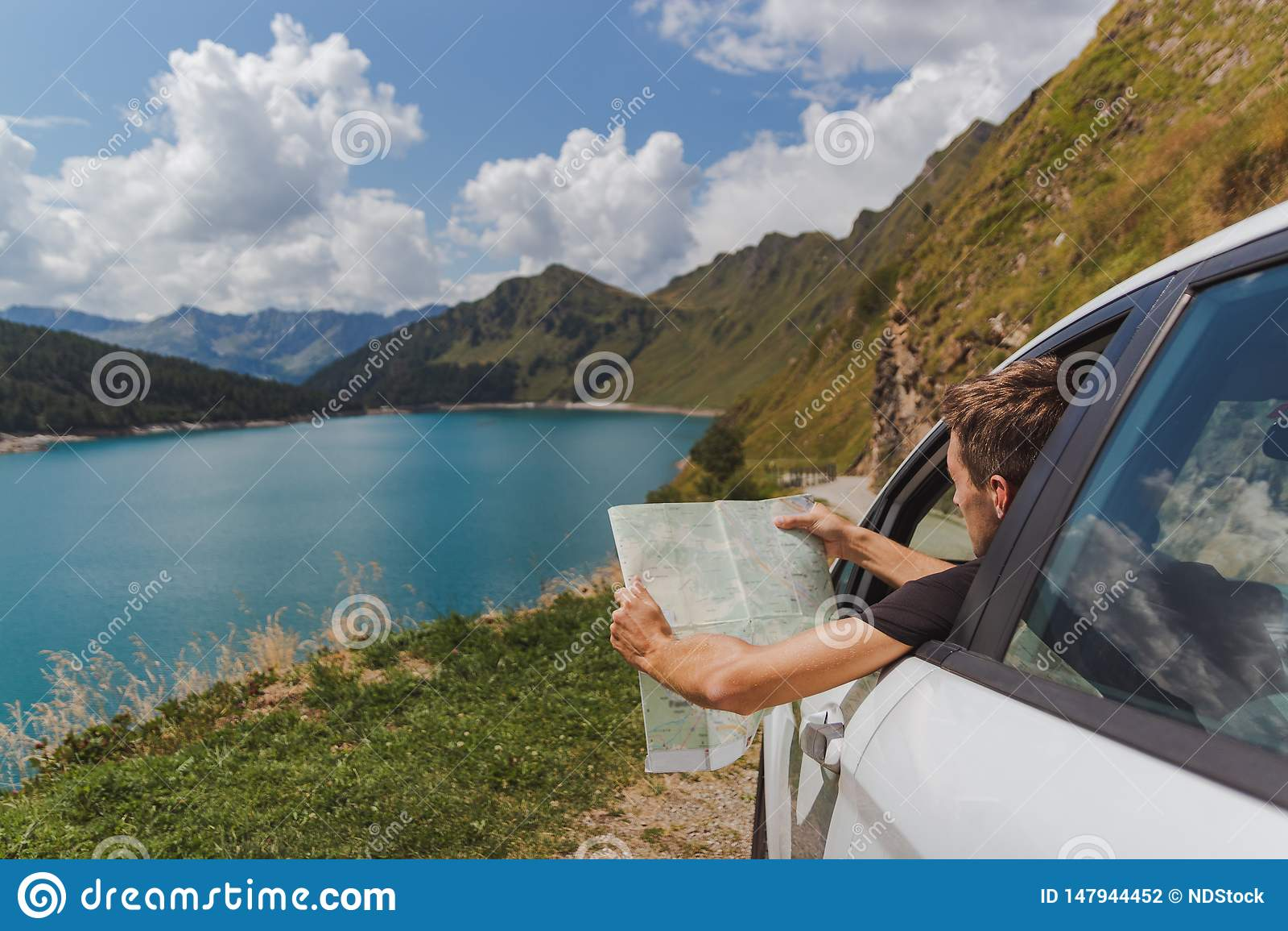 Le jeune homme a perdu dans les montagnes avec sa voiture regardant la carte pour trouver la route droite
