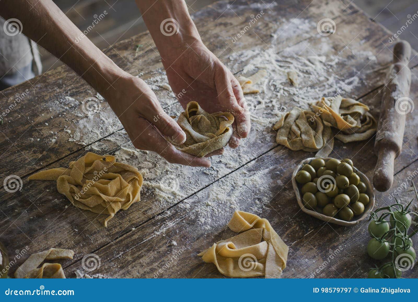 Le jeune homme prépare les pâtes faites maison à la cuisine rustique