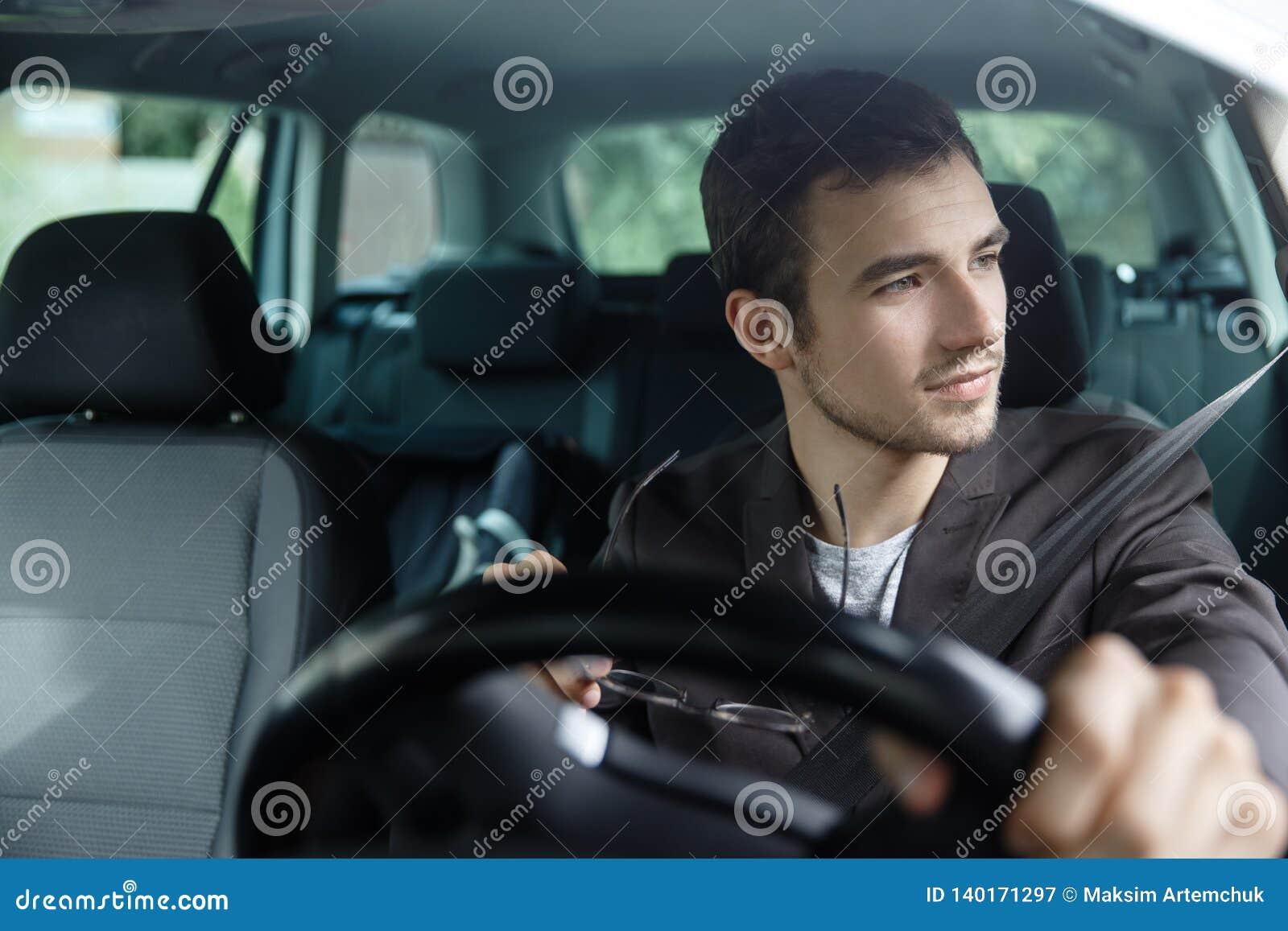 Le jeune homme ravi regarde la cuvette la fenêtre tout en conduisant sa voiture Il tient ses verres à sa main droite Sa main gauc