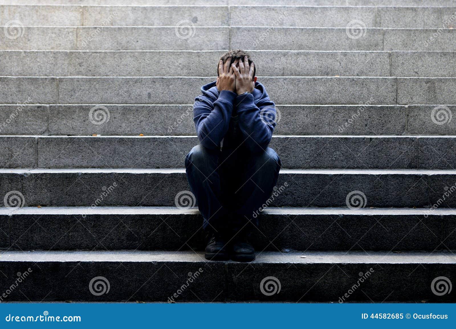 Le jeune homme sans abri a perdu le travail se reposant dans la dépression sur les escaliers moulus de béton de rue
