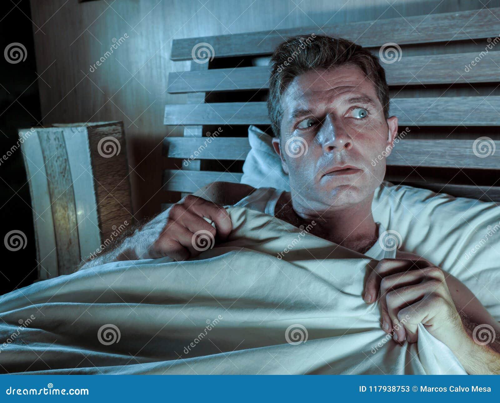 Le jeune homme sans sommeil se situant dans le lit a soumis à une contrainte et a effrayé le cauchemar de souffrance et couette d