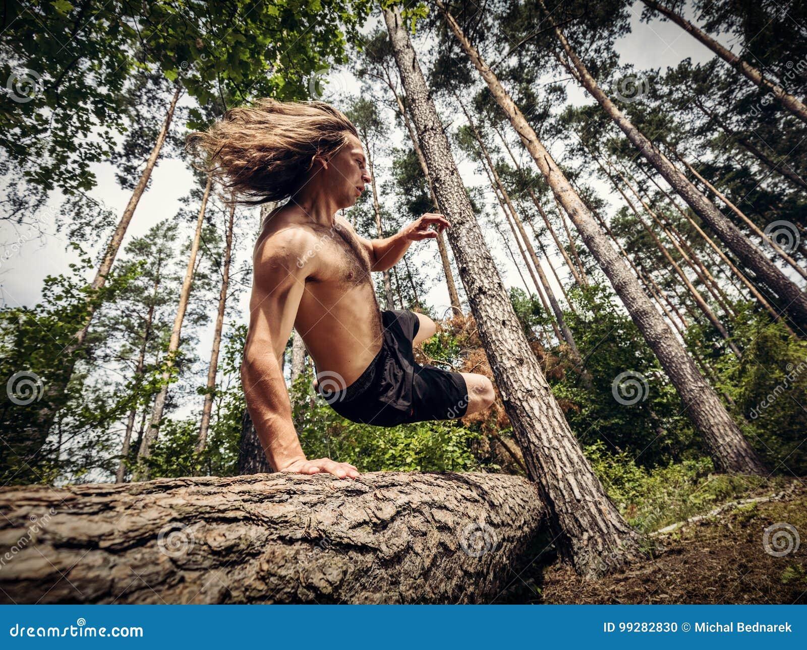 Le jeune homme sautant par-dessus un tronc d arbre dans la forêt