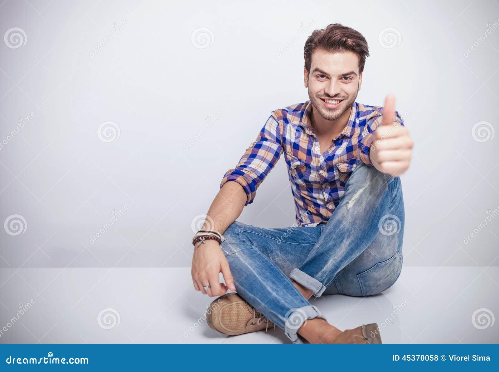 Le jeune homme souriant tout en montrant les pouces lèvent le geste