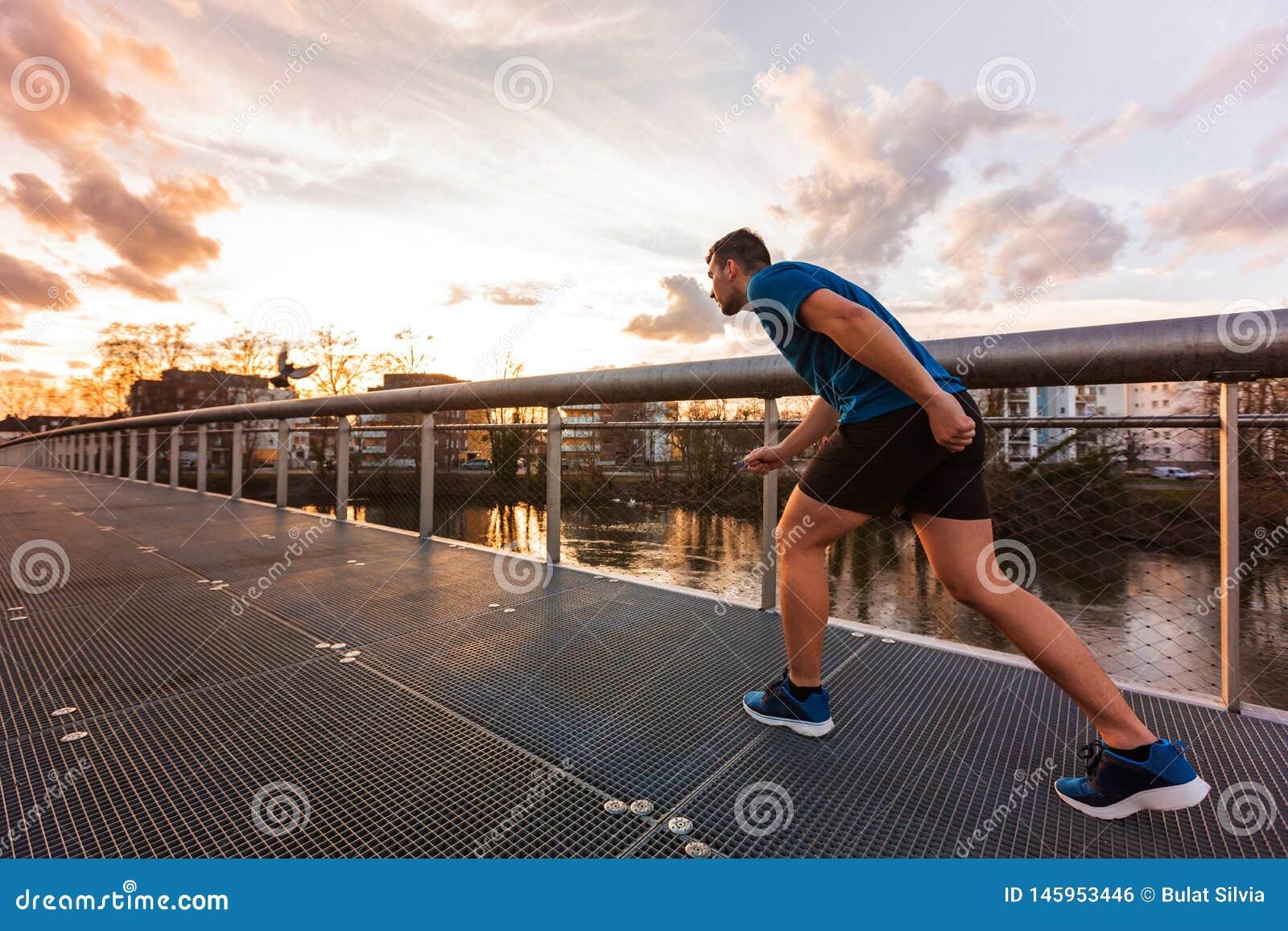 Le jeune homme sportif se préparent à un sprint couru