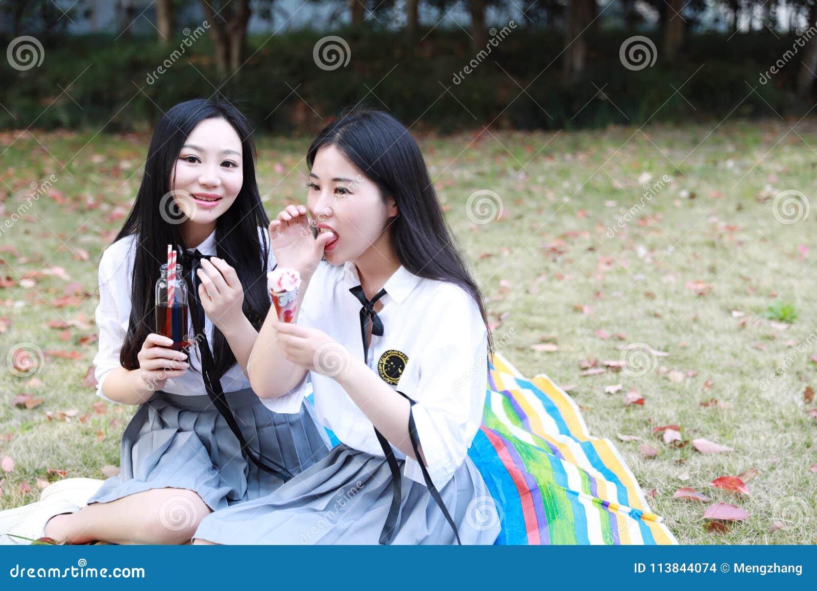 Le jeune joli costume chinois asiatique d étudiant d usage de filles à l école mangent l eau de kola d orangeade de fruit de glac