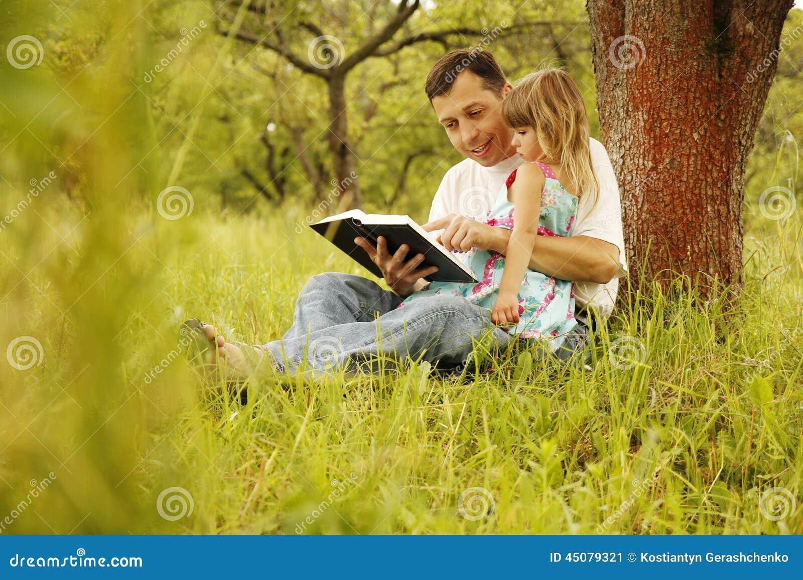 Le jeune père avec sa petite fille lit la bible