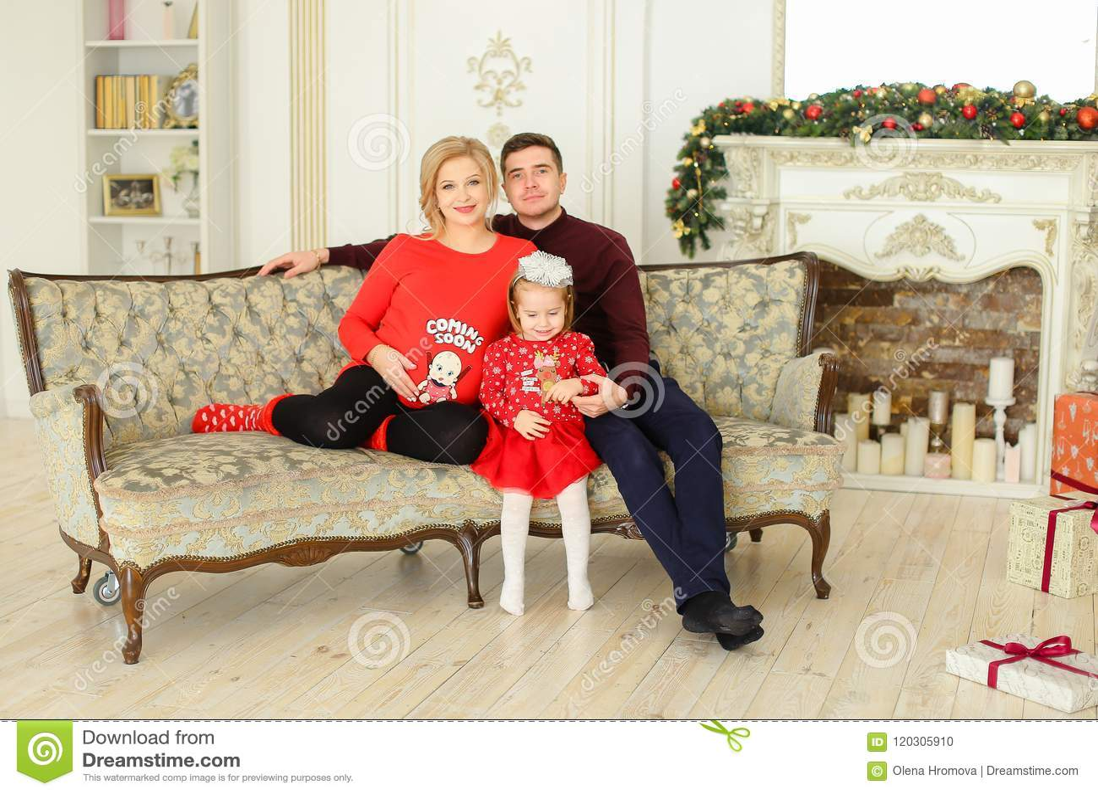 Le jeune père et la mère enceinte s asseyant avec la petite fille sur le sofa près ont décoré la cheminée