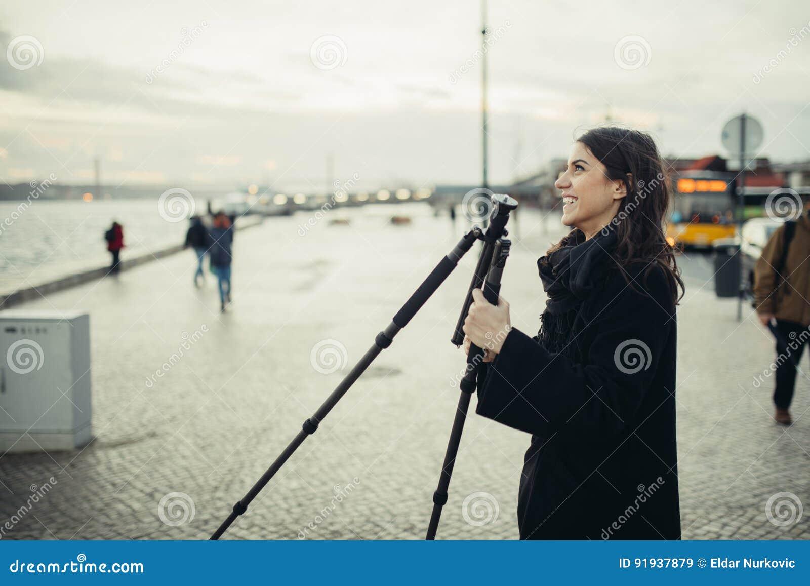 Le jeune photographe féminin enthousiaste installant le trépied léger de voyage de carbone pour l exposition de rondin de coucher