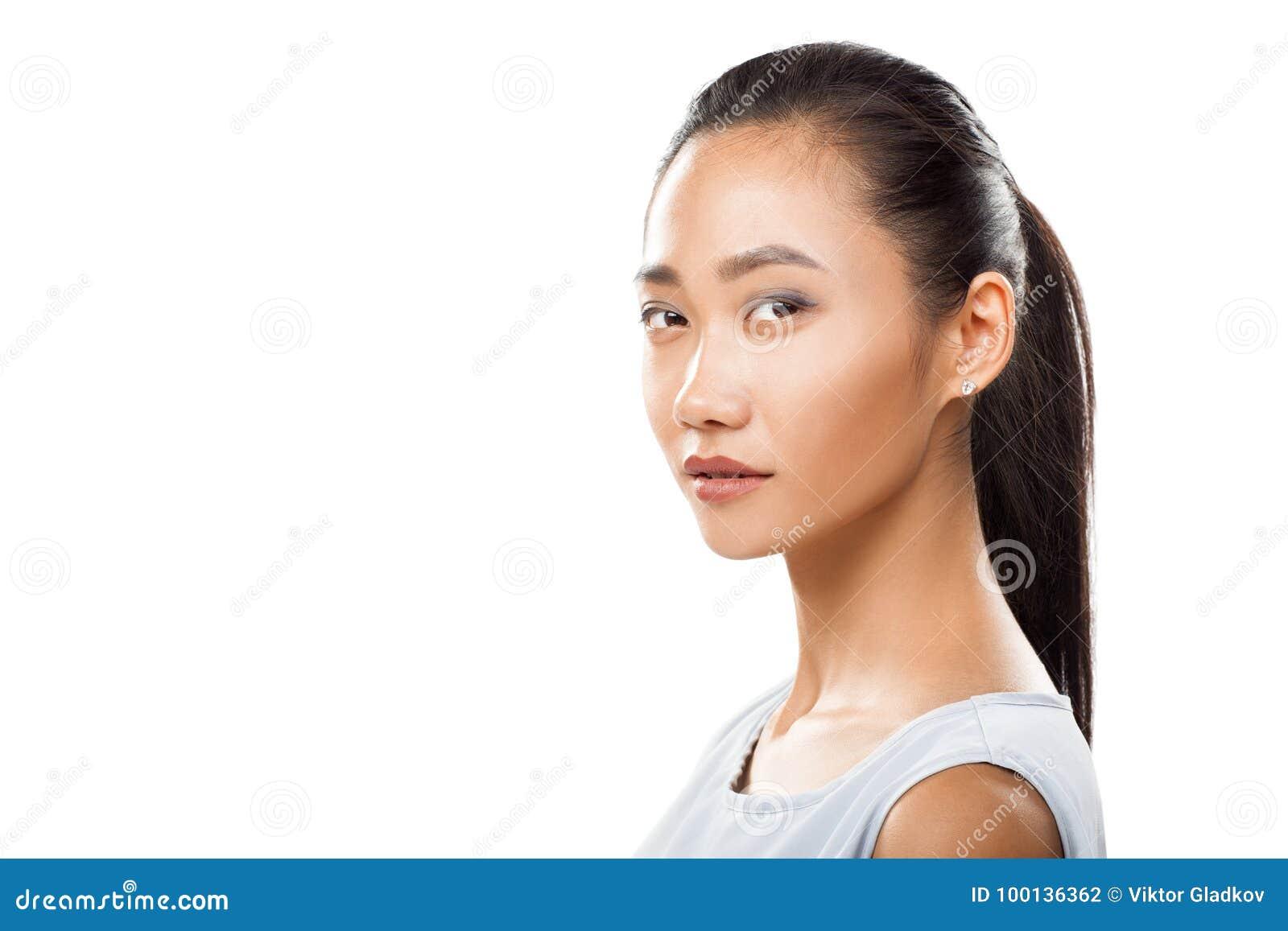 Le jeune plan rapproché asiatique de femme a tourné la tête et regarder l appareil-photo