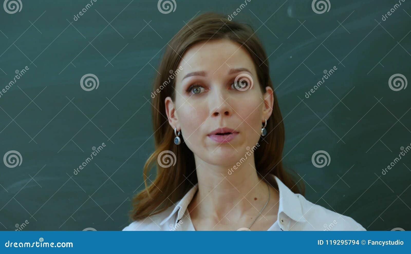 Le jeune professeur féminin disent intéressant pour classer près du tableau noir