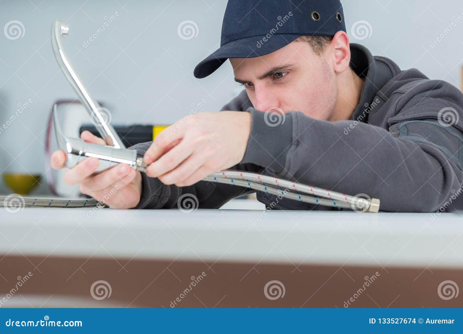 Le jeune robinet beau de fixation de plombier aux cleints autoguident