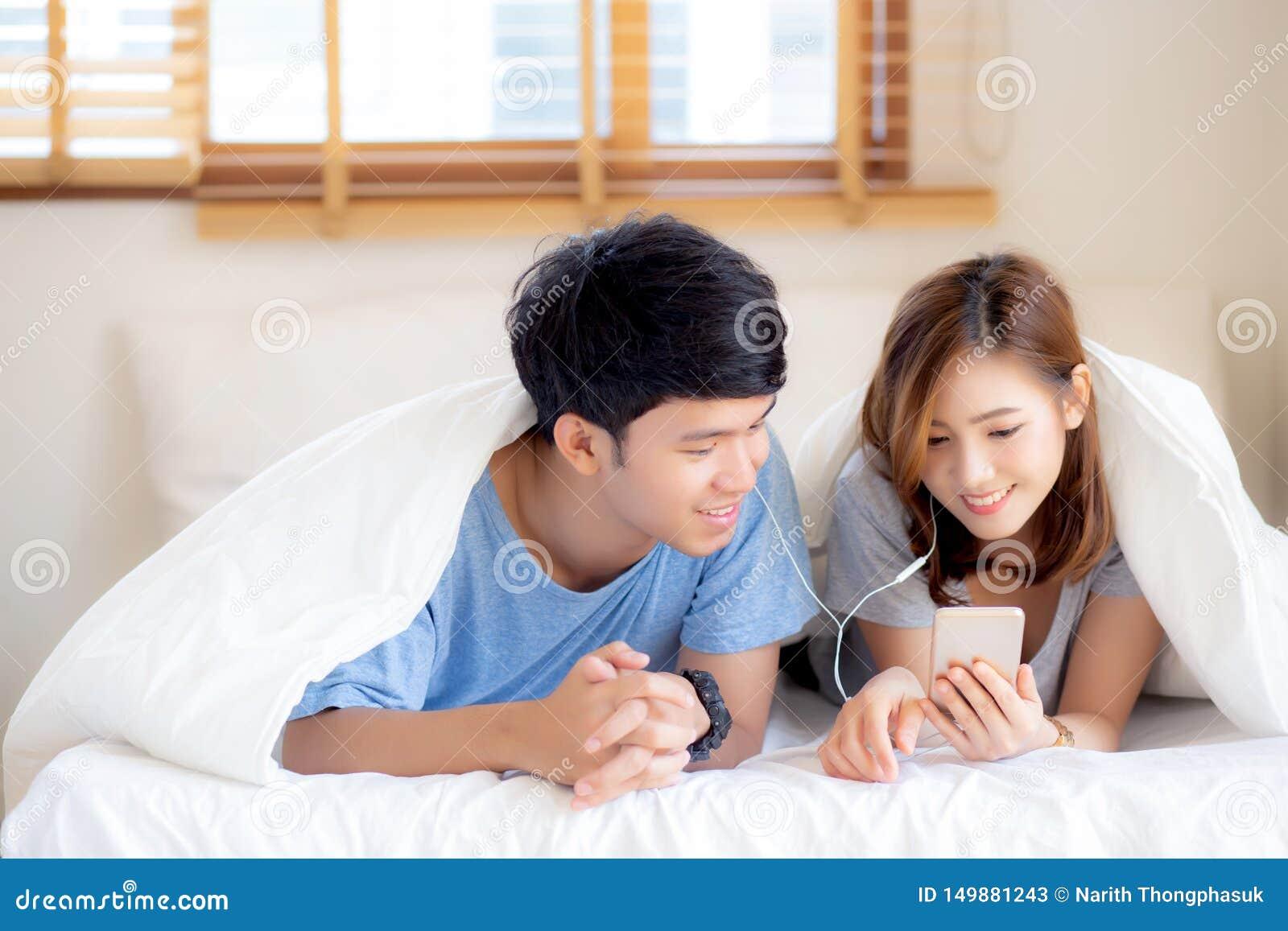 Le jeune sourire asiatique de couples écoutent musique avec le téléphone portable intelligent sur le lit à la chambre à coucher a
