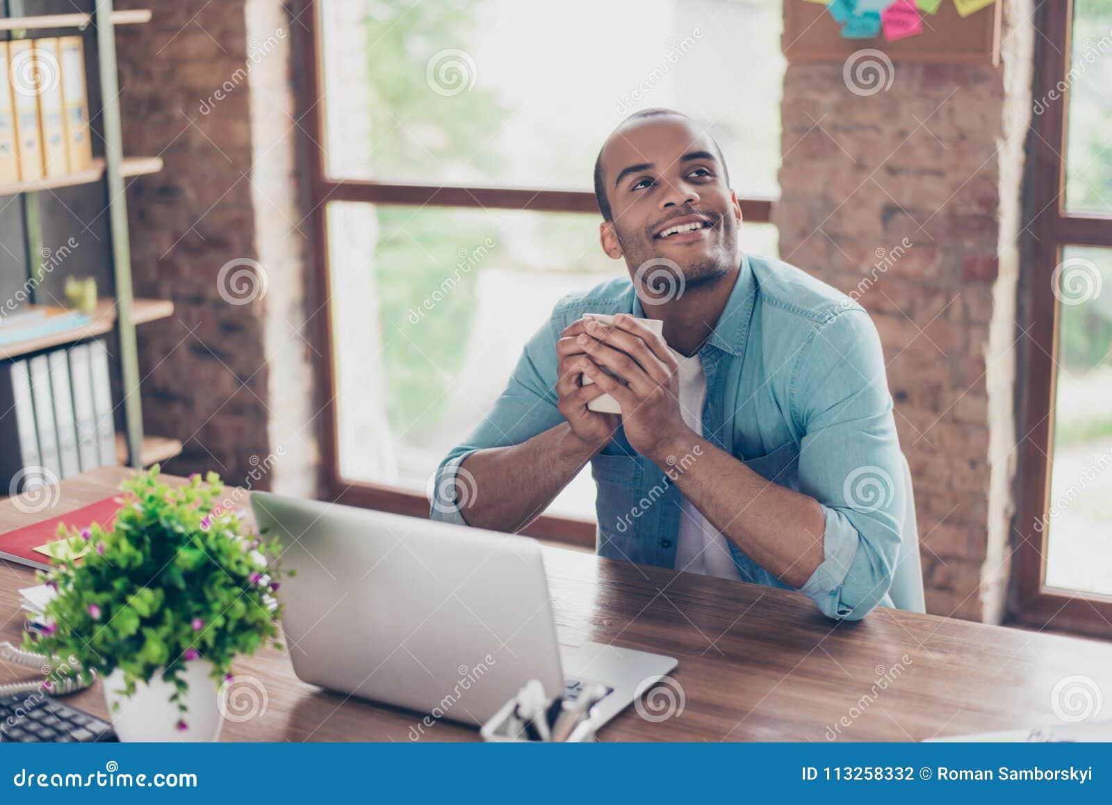 Le jeune travailleur américain rêvant de mulâtre pense devant l ordinateur portable au lieu de travail Il est heureux, souriant,