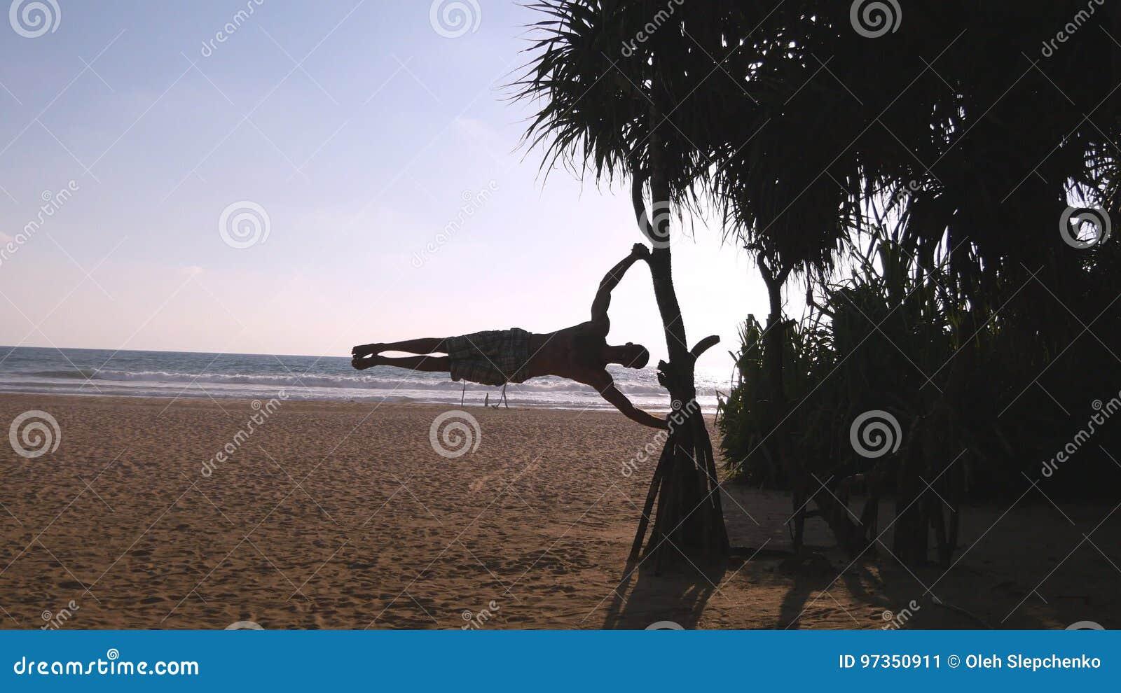 Le jeune type démontre le drapeau humain à la plage de mer Homme sportif faisant des éléments de gymnastique sur le palmier à l o