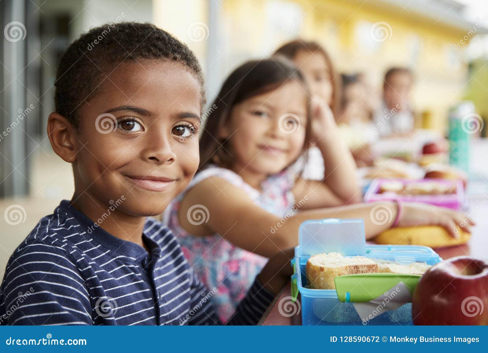 Le jeunes garçon et fille au repas scolaire ajournent le sourire à l appareil-photo