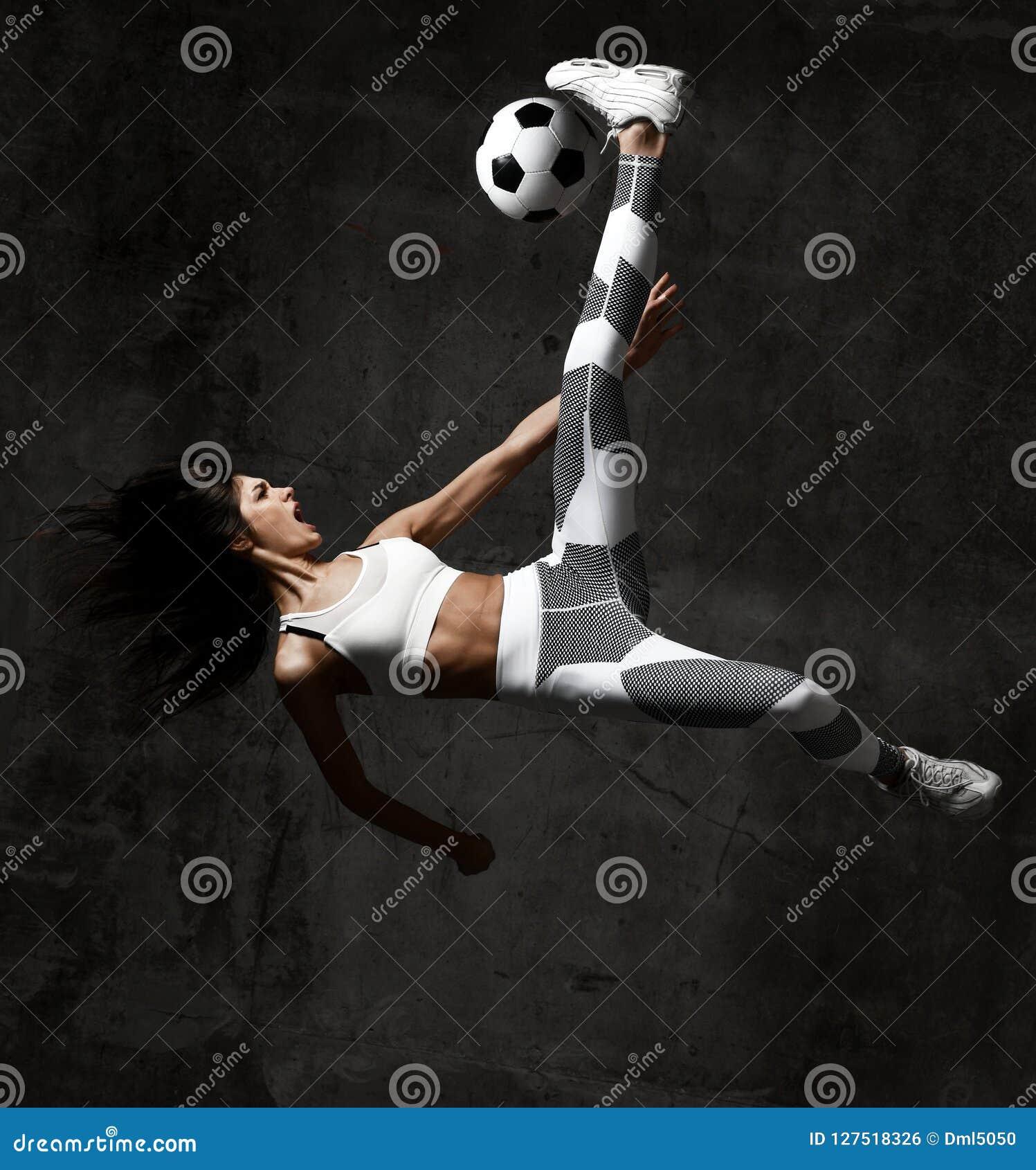 Le joueur de femme du football saute et a frappé la boule hurlant des cris sur le mur en béton de grenier