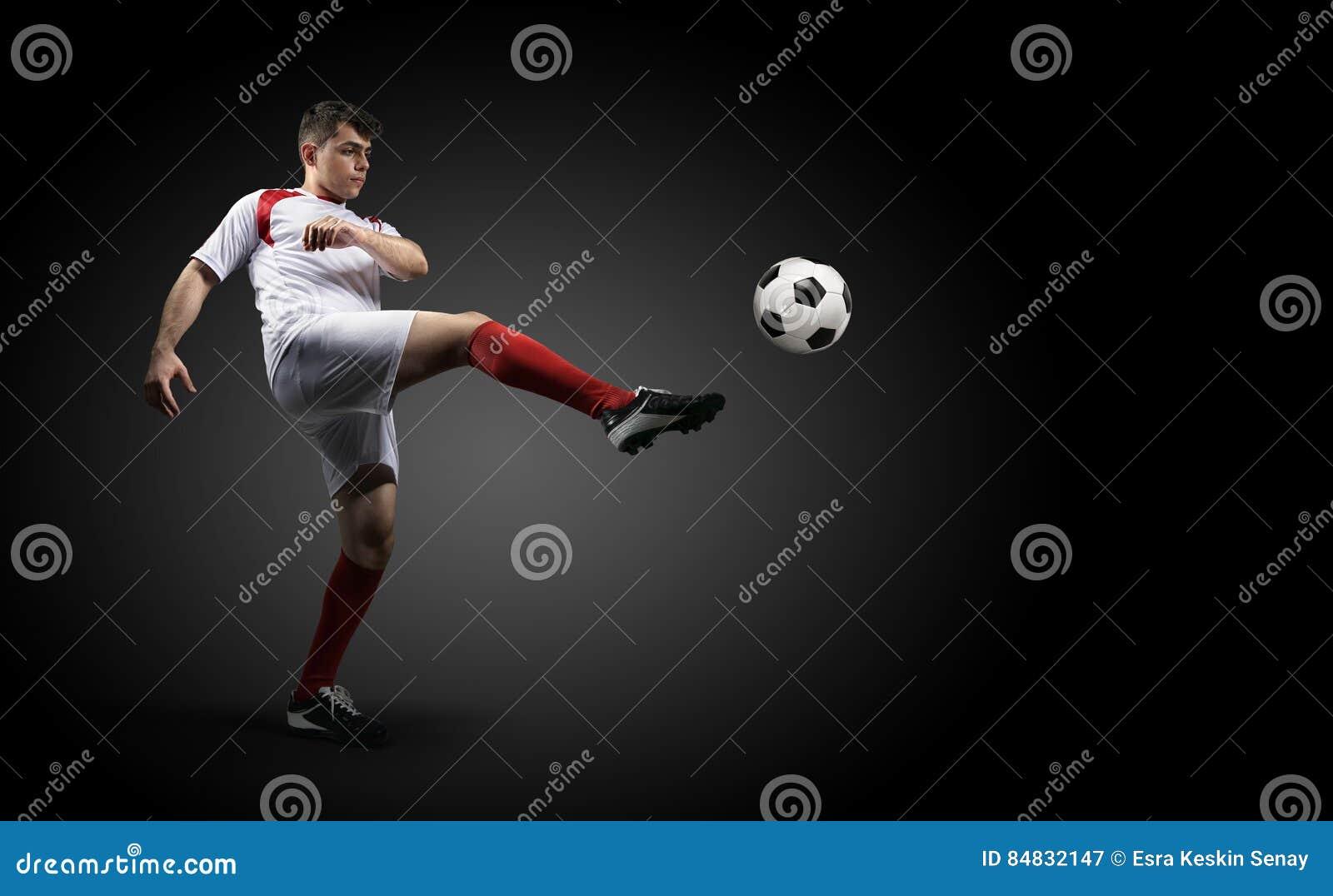 Le joueur de football donne un coup de pied une boule sur le fond noir