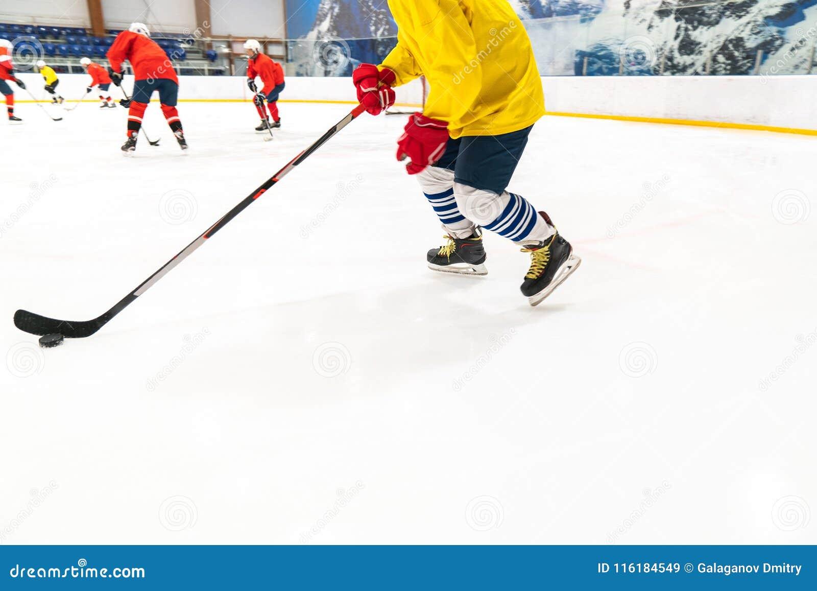 Le joueur de hockey dans un dessus et des gants rouges de réservoir jaune pour des personnes conduit le galet Le jeu de formation