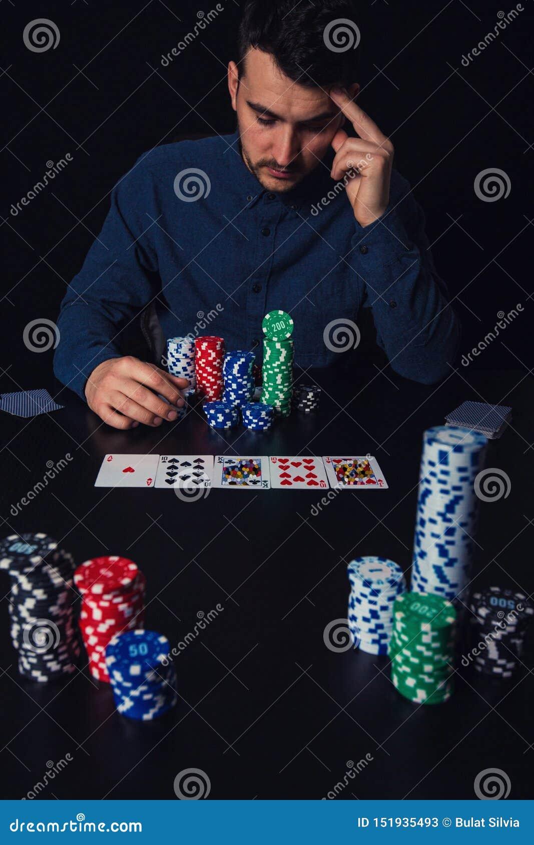 Le joueur de poker songeur d homme assis à la table de casino, garde la main au front, pensant regarde aussi en tant que les cart