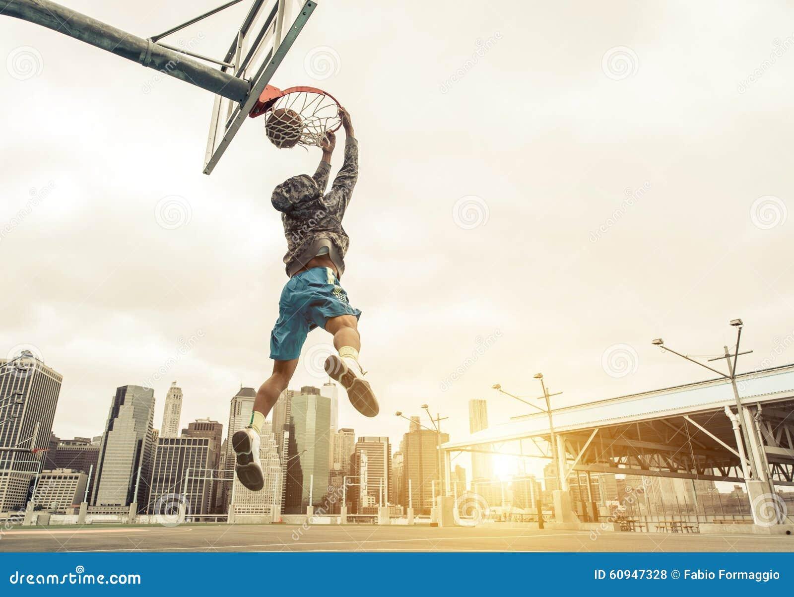 Le joueur de rue de basket-ball faisant un claquement arrière trempent