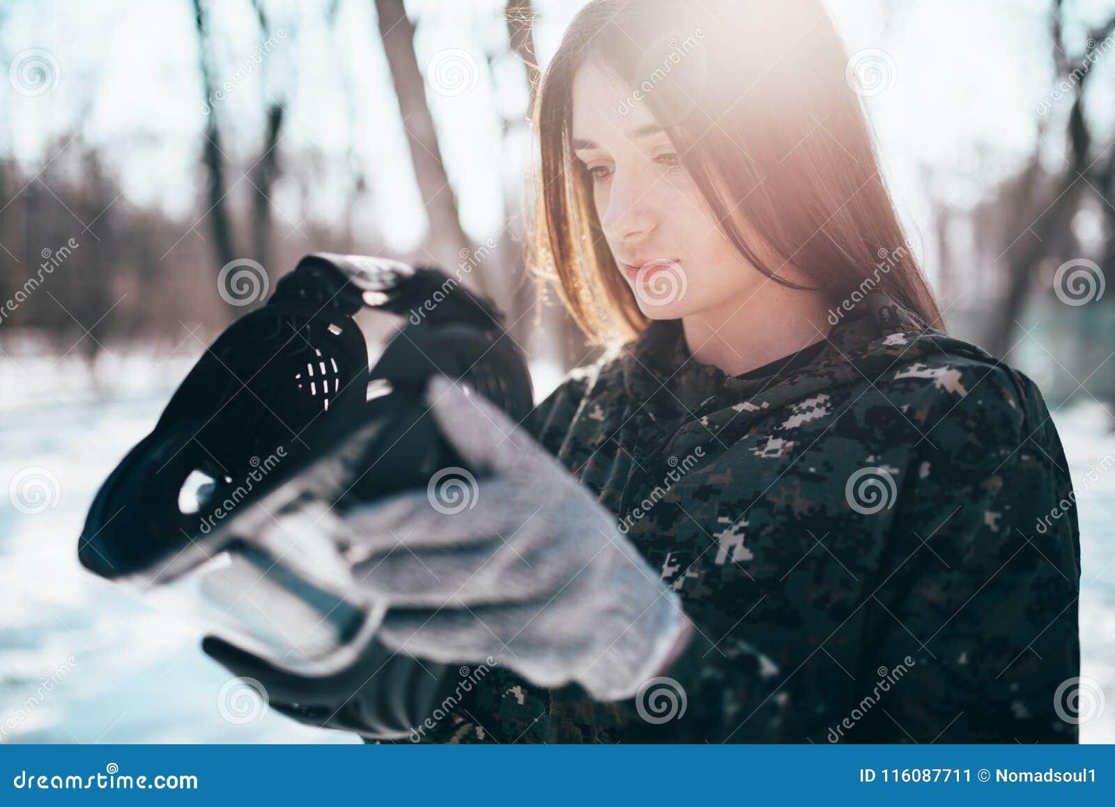Le joueur féminin de paintball met dessus le masque de protection