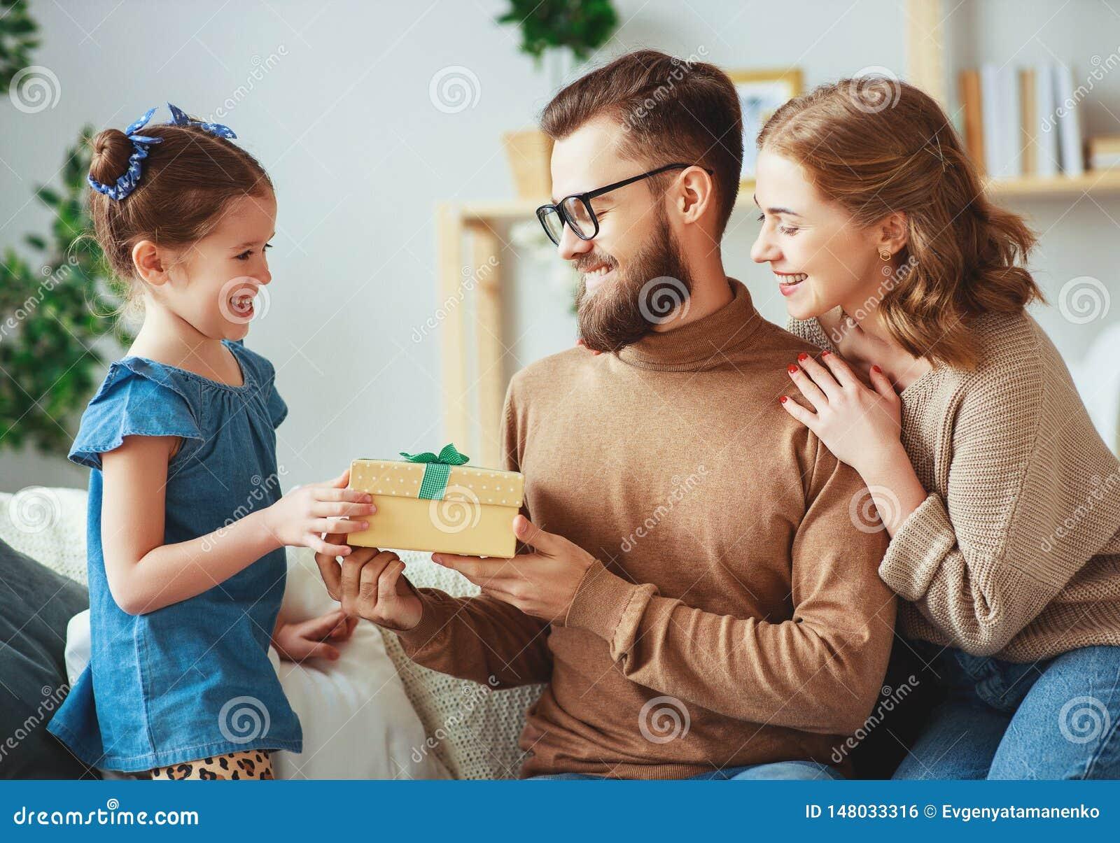 Le jour de p?re heureux ! maman et fille de famille f?liciter le papa et donner le cadeau