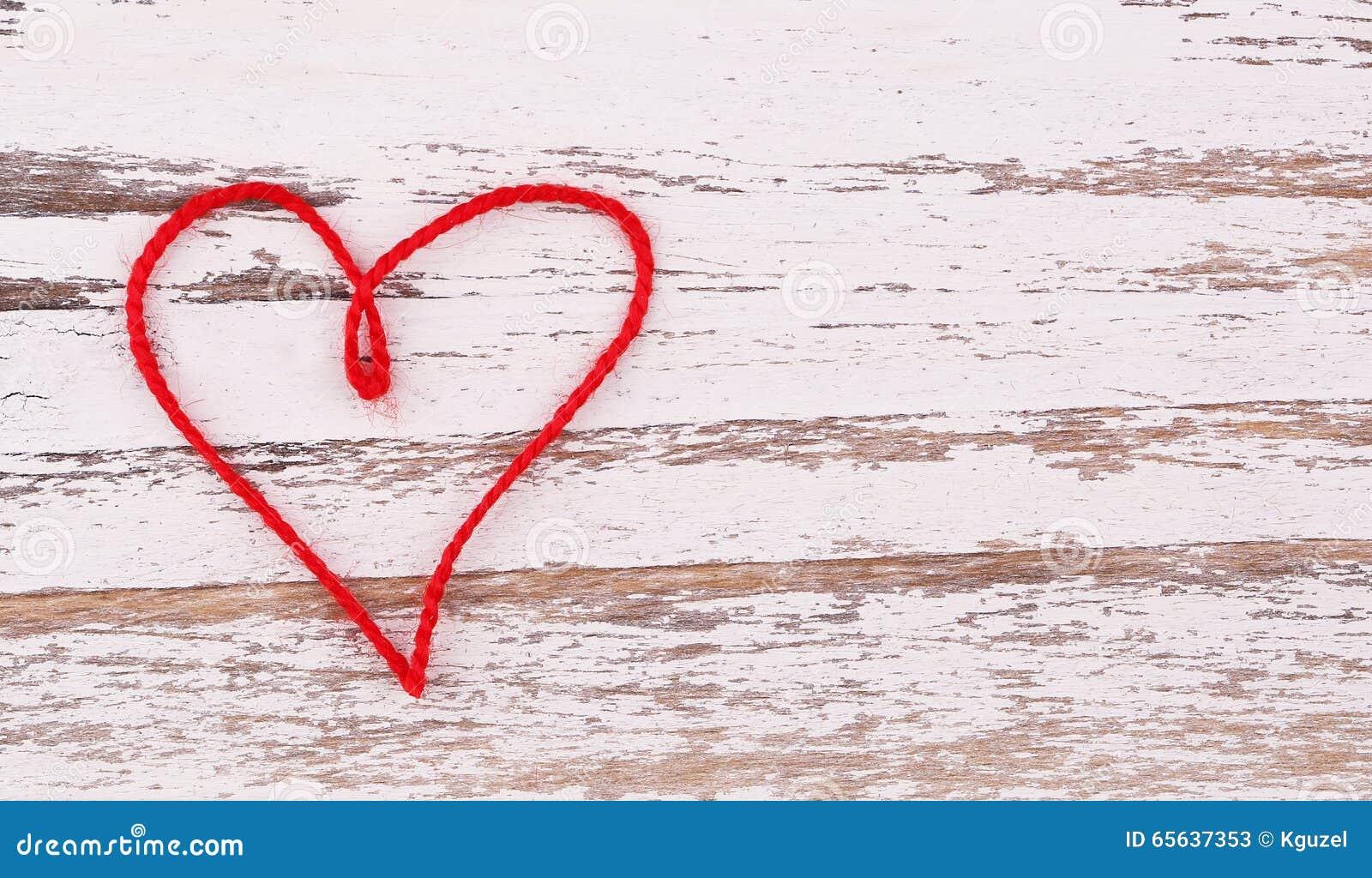 Le jour de Valentine Le coeur rouge du fil a formé sur le fond en bois