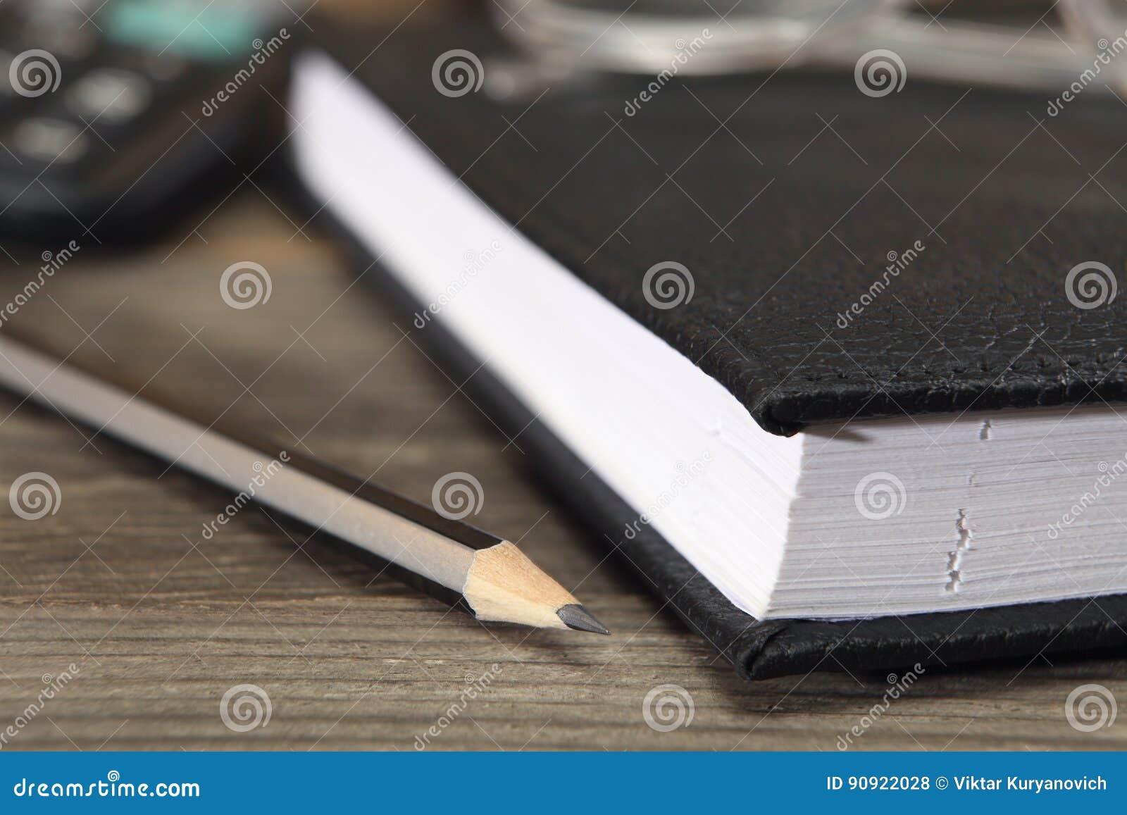 Le journal intime et un crayon noir simple se trouvent sur le
