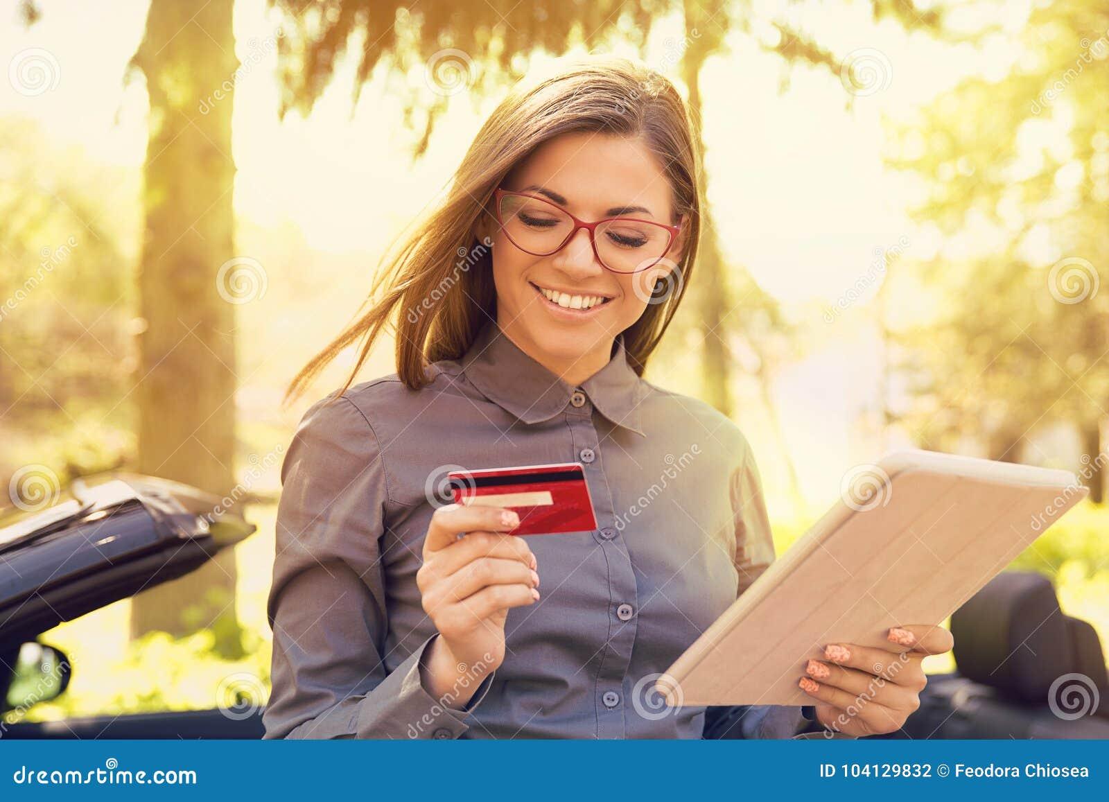 Le kvinnaanseende av hennes bil som gör online-betalning på hennes minnestavladator utanför på en sommardag