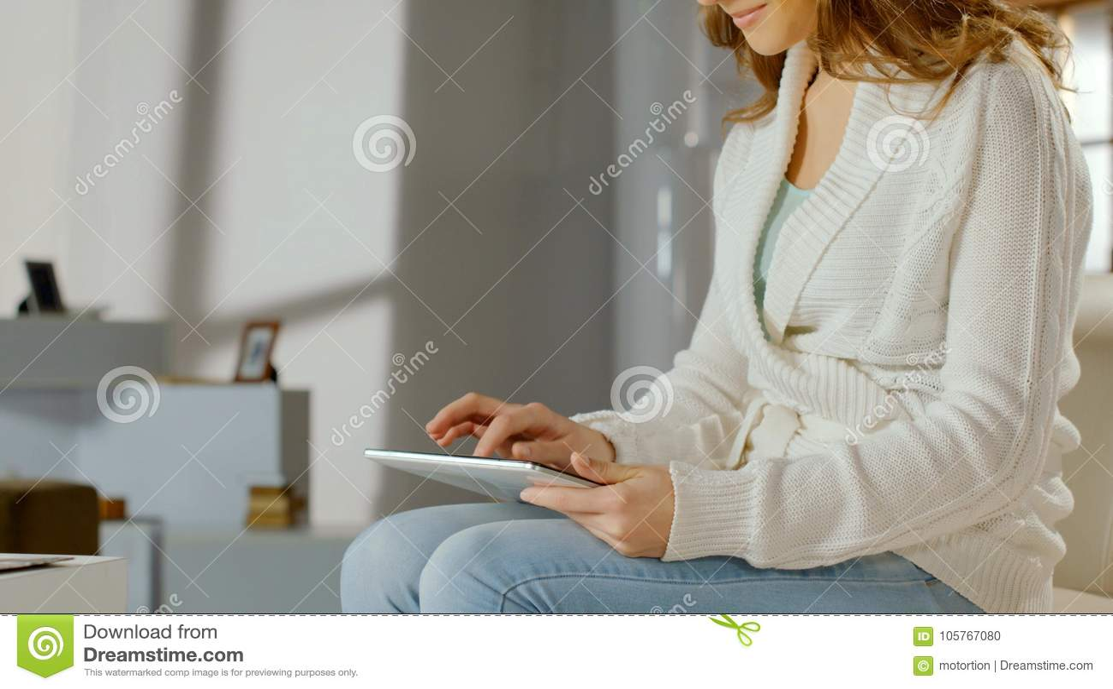 Le kvinnan som använder app på den hemmastadda minnestavlaPC:N och att prata direktanslutet, hållande ögonen på filmer